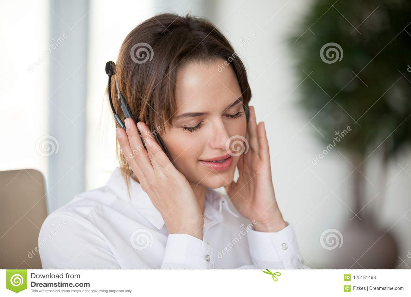 De jonge vrouw die in hoofdtelefoons van prettige goede muziek genieten voor ontspant