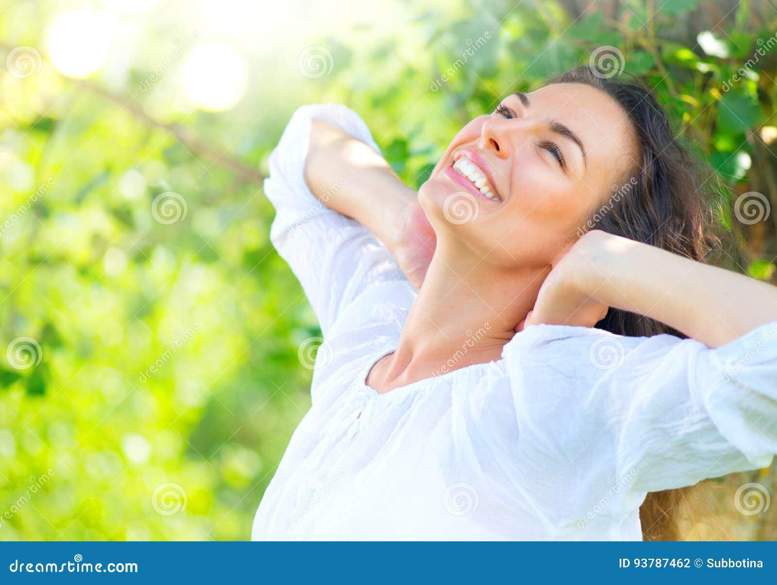 De jonge vrouw die van de schoonheid van aard geniet