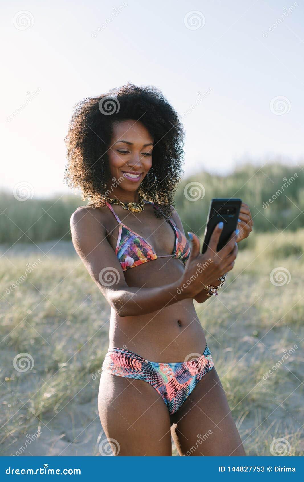 De jonge vrouw die van het afrohaar selfie bij het strand nemen