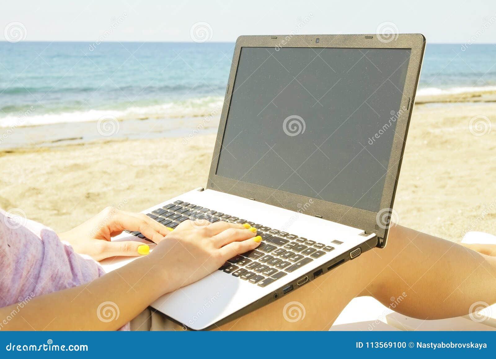 De jonge vrouw die van het blondehaar aan laptop bij het strand op zonnige dag werken Sluit omhoog van vrouwelijke handen typend