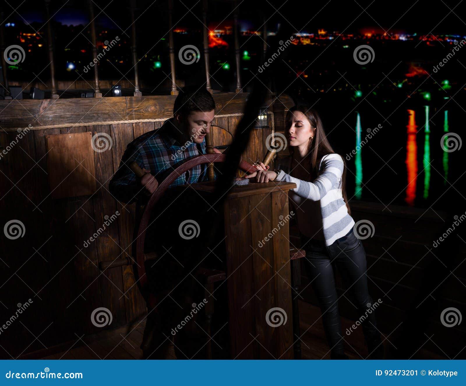 De jonge vrouw en de man bevinden zich bij het roer van het schip en bekijken Th