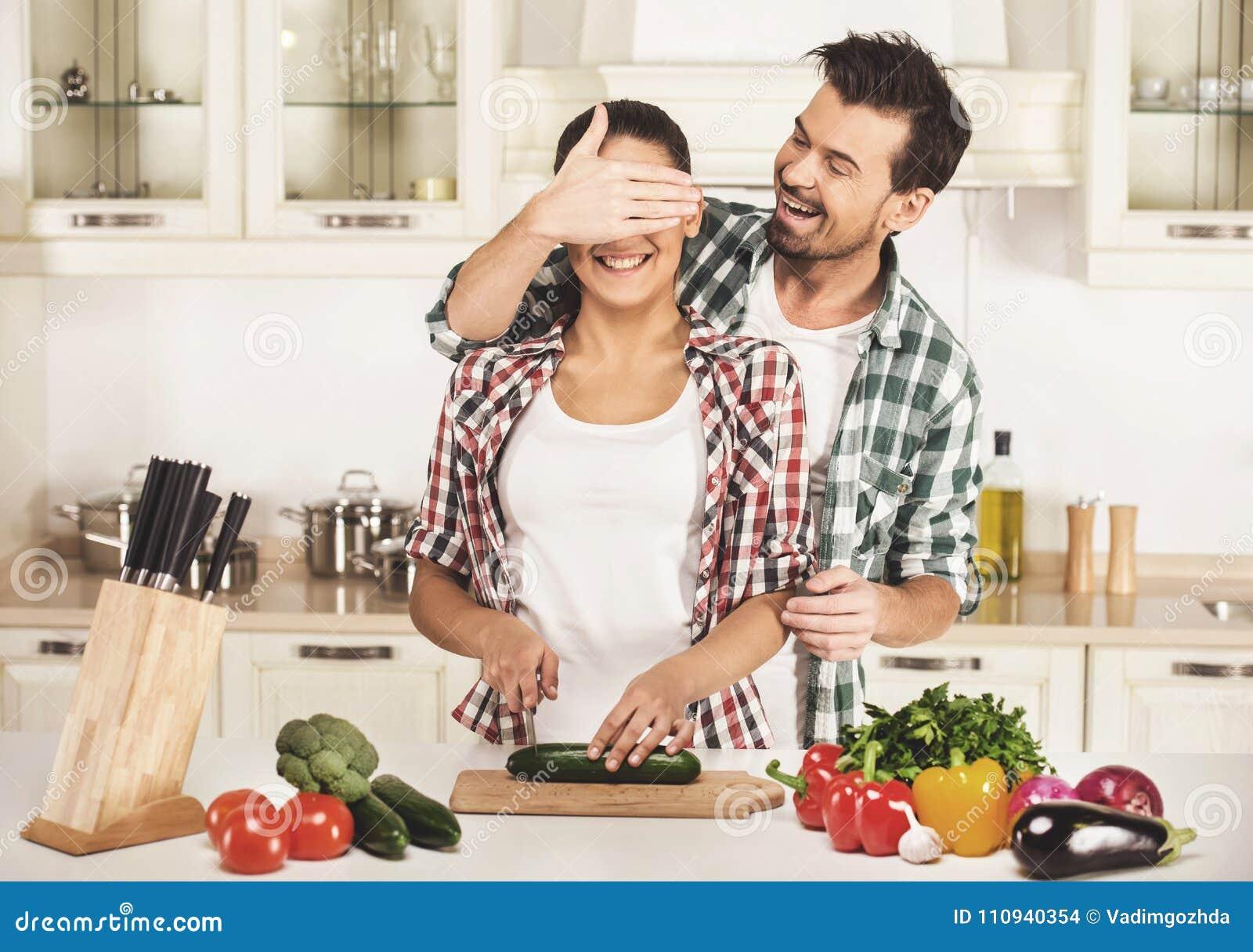 De jonge vrouw en de echtgenoot koken met verse groenten De echtgenoot sluit haar ogenhand