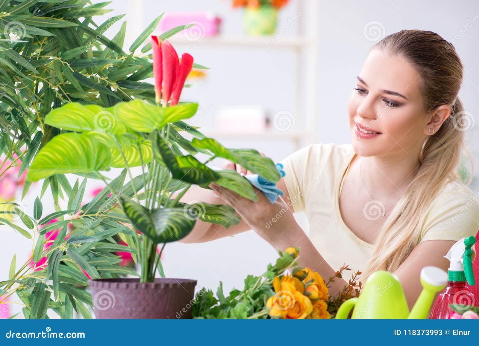 De jonge vrouw het water geven installaties in haar tuin