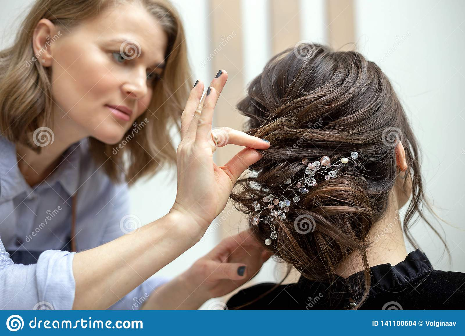 De jonge vrouw krijgt een kapsel bij een salon