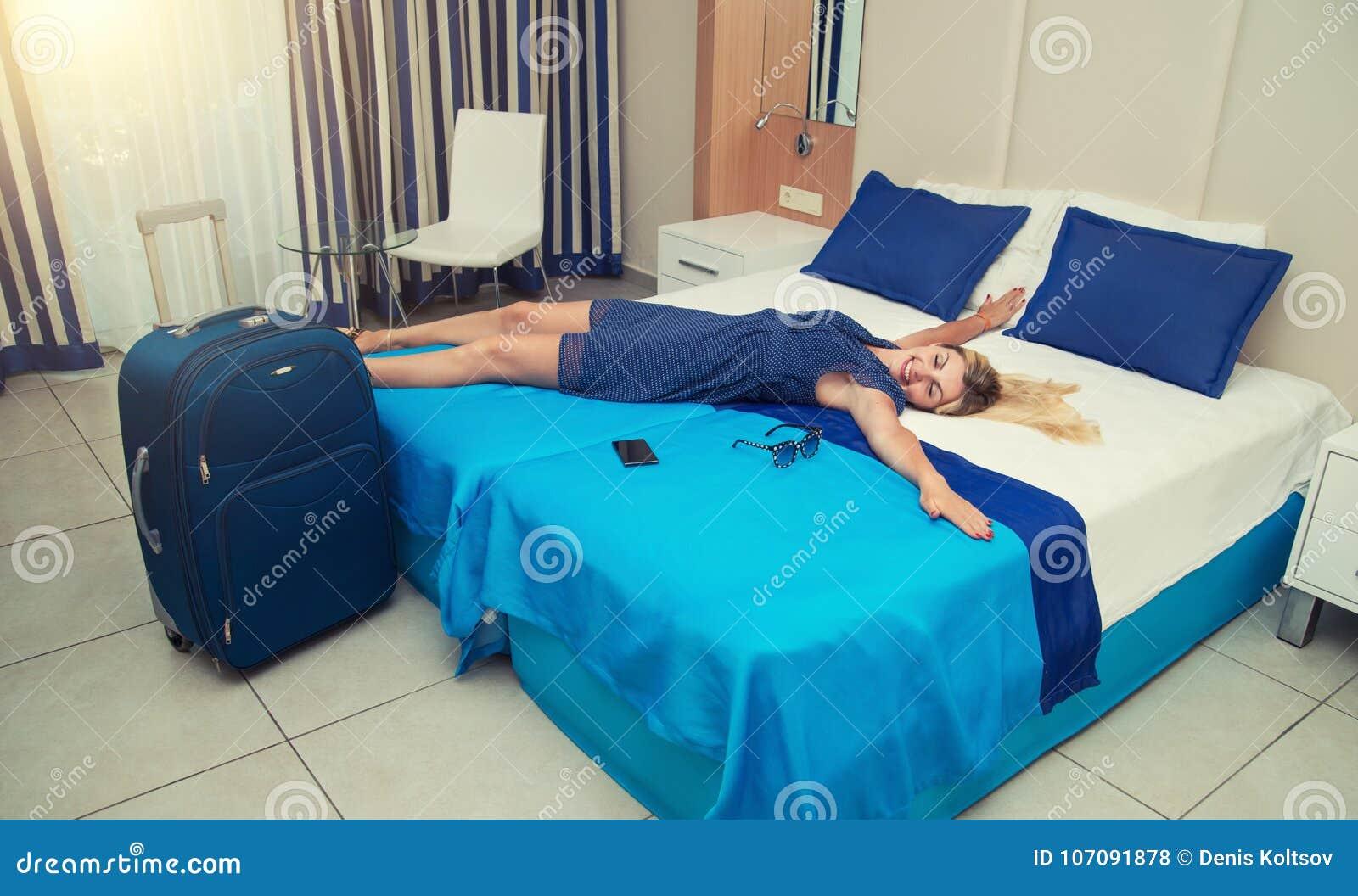 De jonge vrouw ligt en heeft een rust op het bed in de hotelruimte