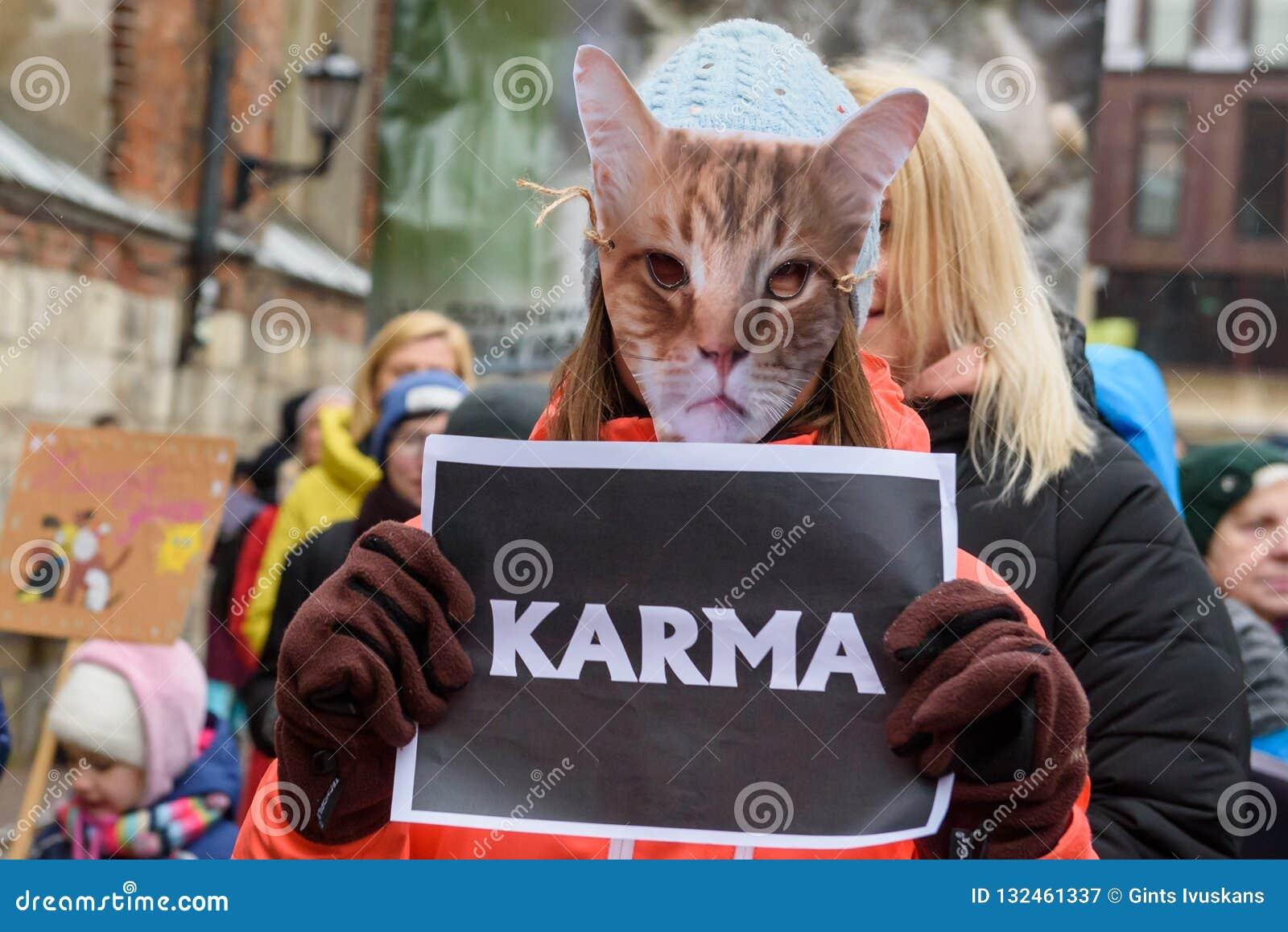De jonge vrouw met kattenmasker op gezicht, heeft een teken KARMA in haar handen, in 'Maart voor dieren in Riga, Letland