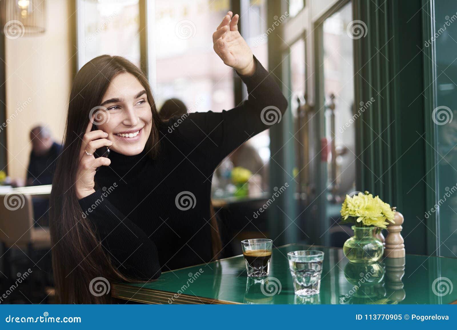 De jonge vrouw met lang haar geeft hallo-vijf aan iemand, drinkt koffie die rust in koffie hebben dichtbij windowing