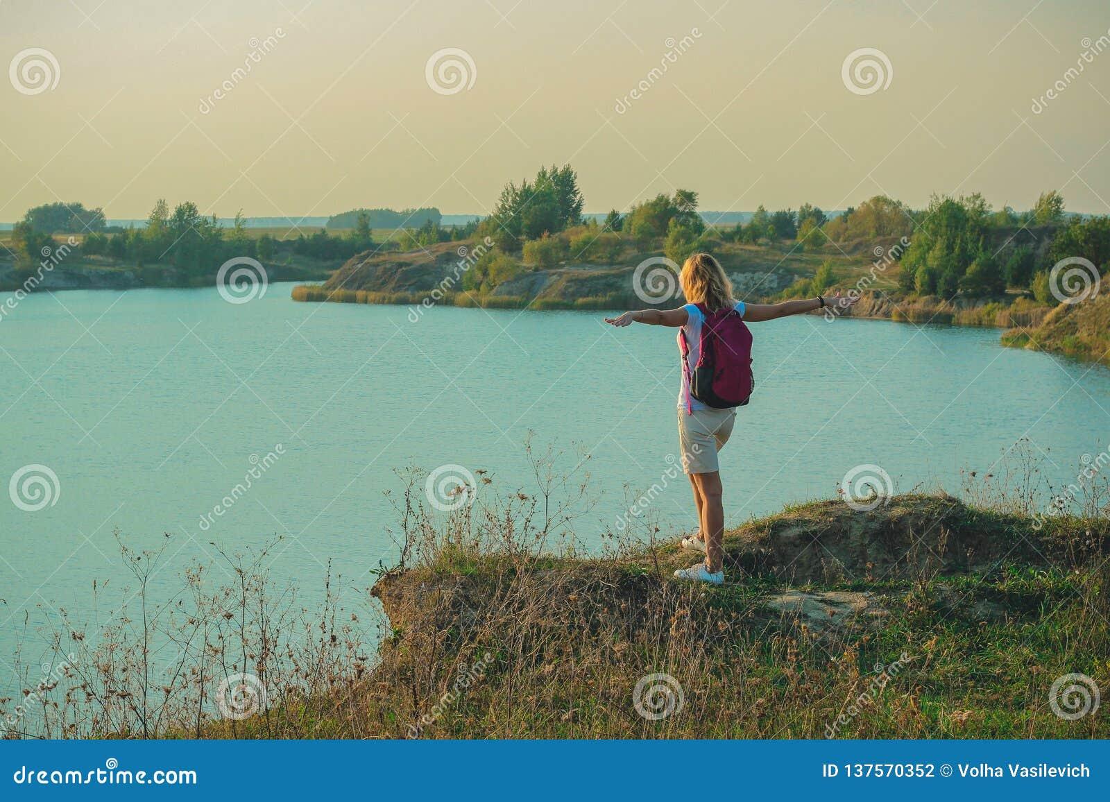 De jonge vrouw met roze rugzak staat op de blauwe achtergrond van krijtsteengroeven dicht in zonsondergangtijd op
