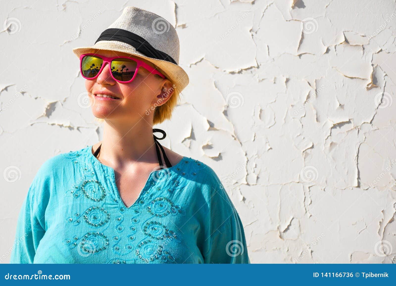 De jonge vrouw met witte hoed en de roze zonnebril kleedden zich in het mooie blauwe overhemd ontspannen