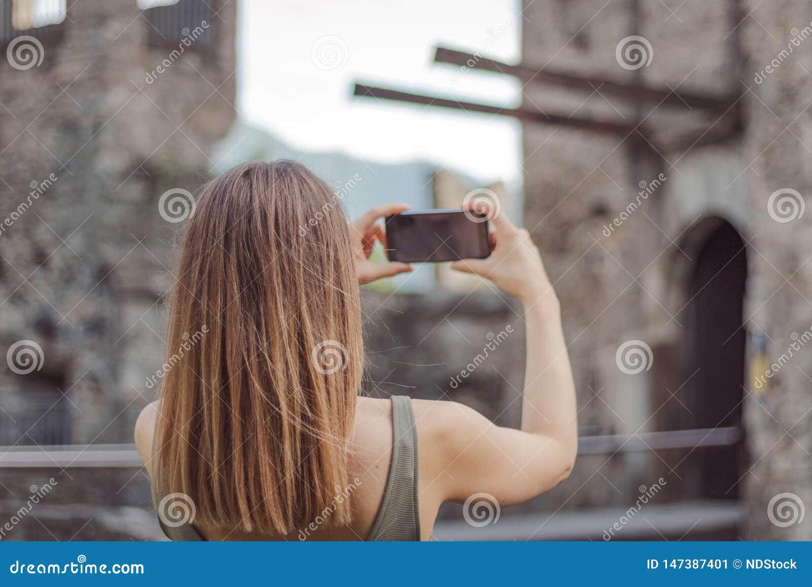 De jonge vrouw neemt een beeld van een kasteel
