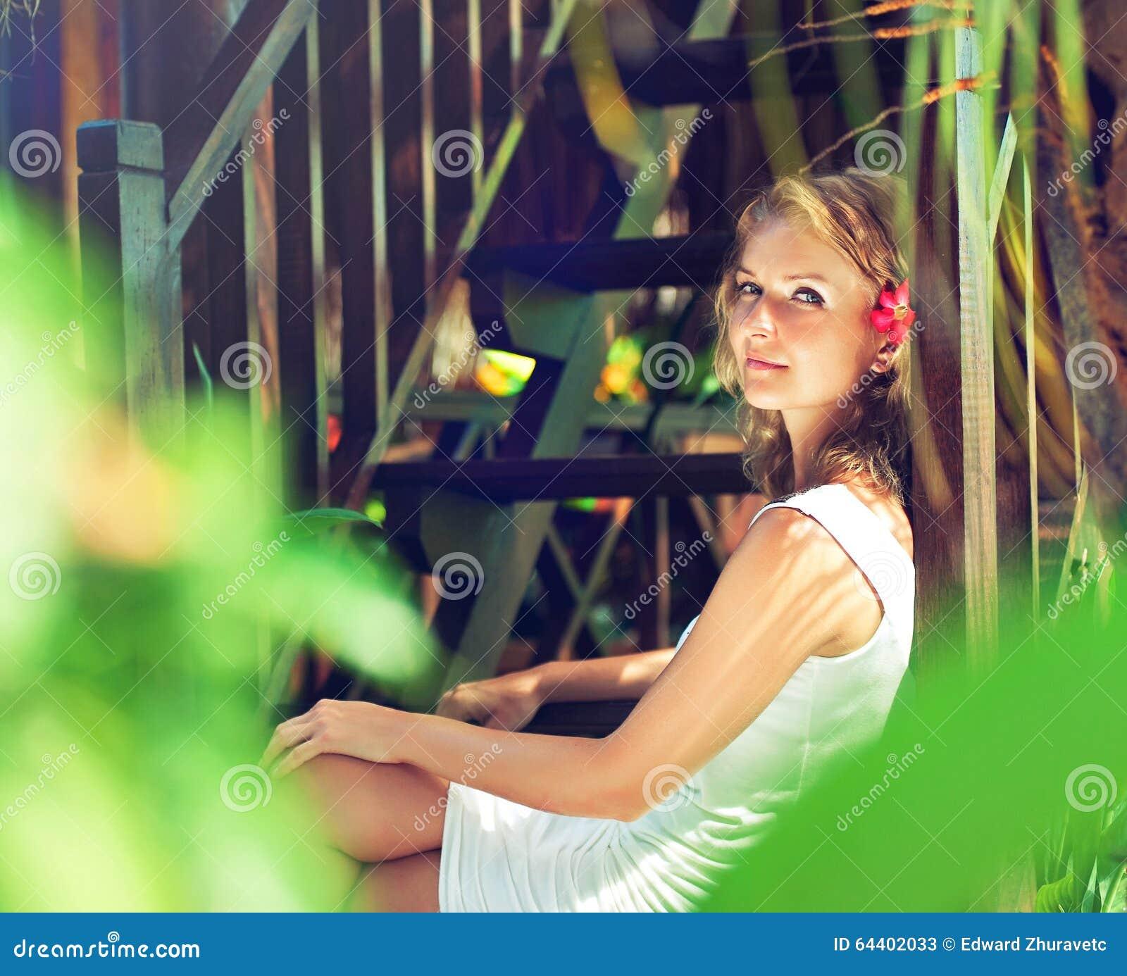 De jonge vrouw, omringde groene installaties