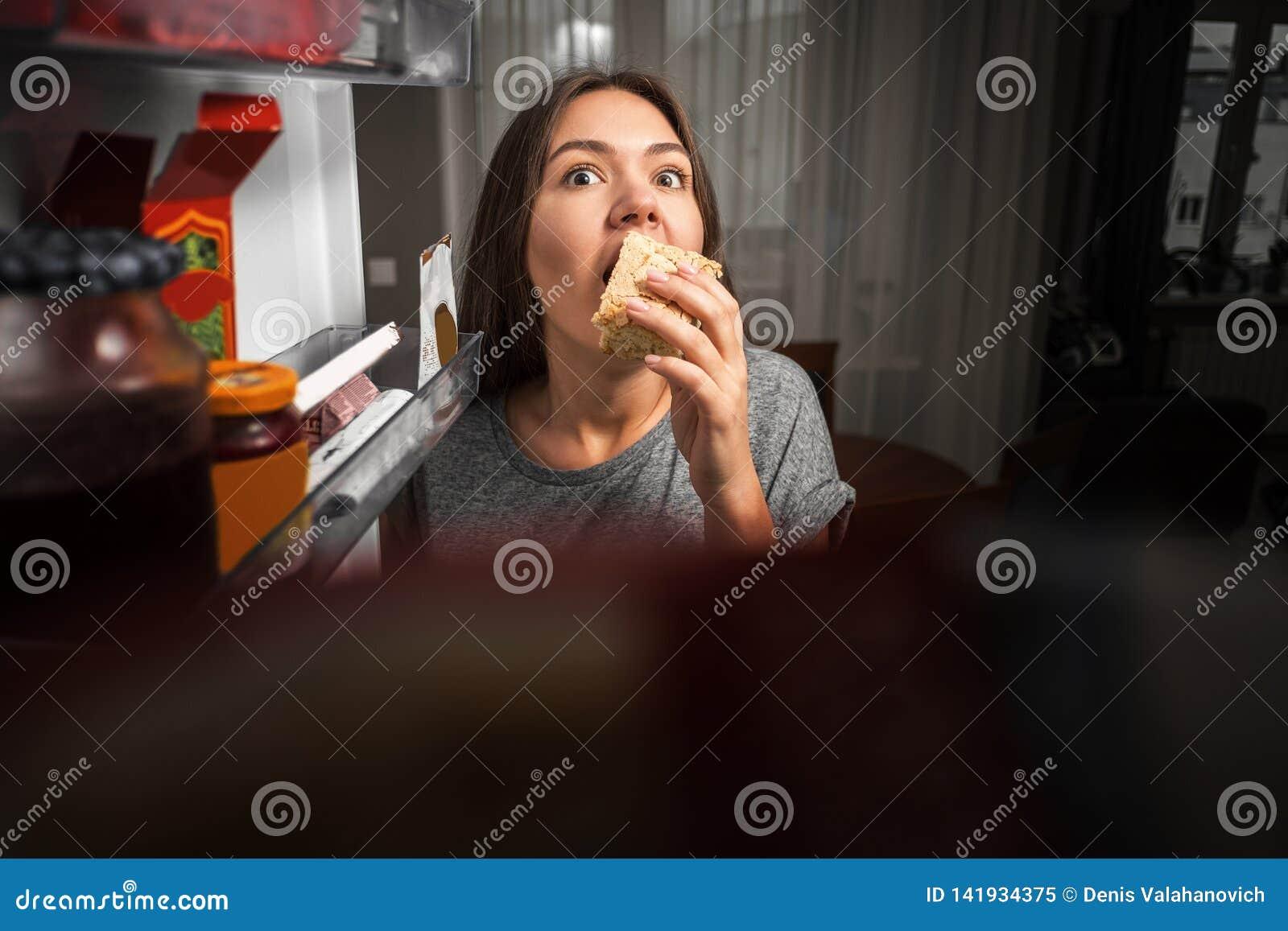 De jonge vrouw onderzoekt de koelkast, mening van koelkast, meisje het eten bij nacht, vrees