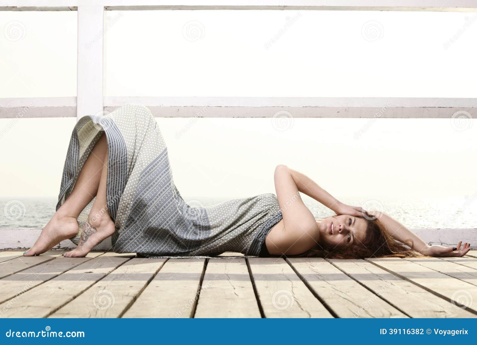 De jonge vrouw ontspant op de pijler