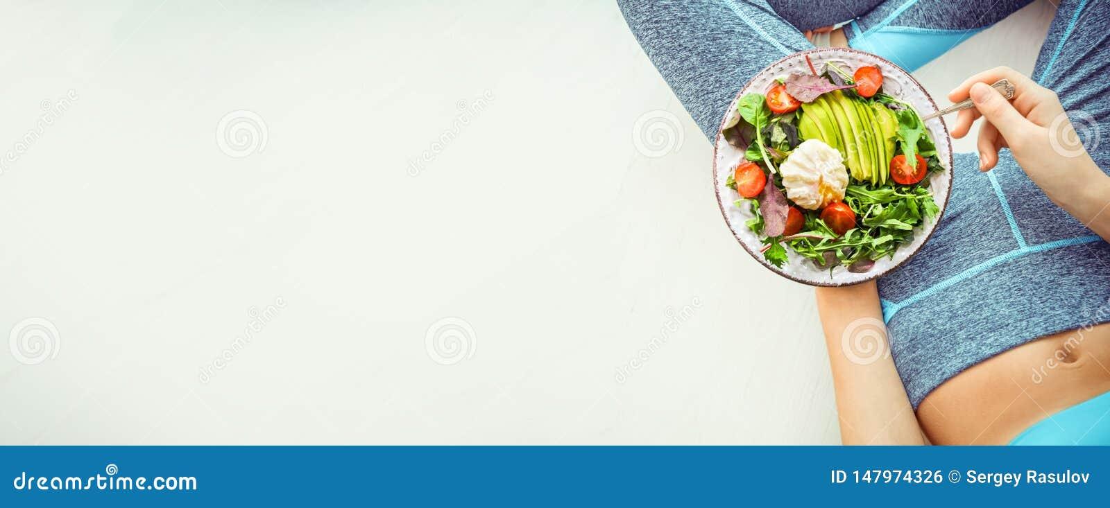 De jonge vrouw rust en eet een gezond voedsel na een training
