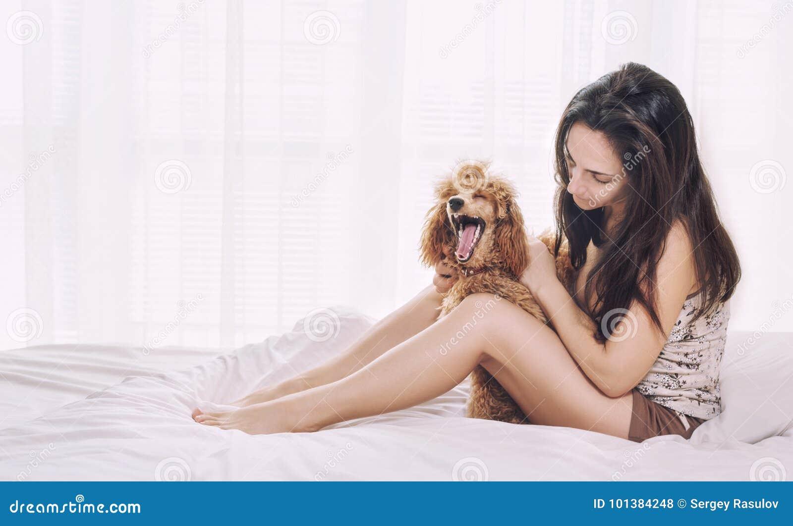 De jonge vrouw rust met een poedelhond op het bed