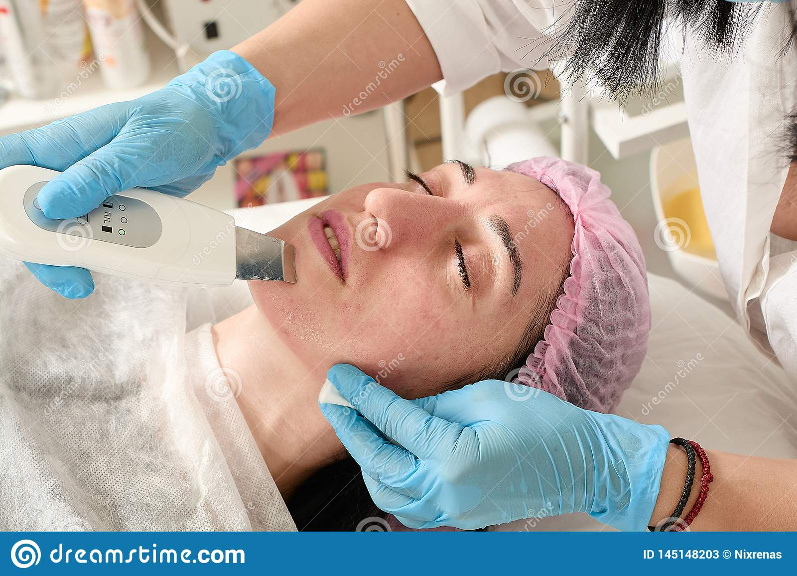 De jonge vrouw in schoonheidssalon doet ultrasone klankschil en gezichts het reinigen procedure