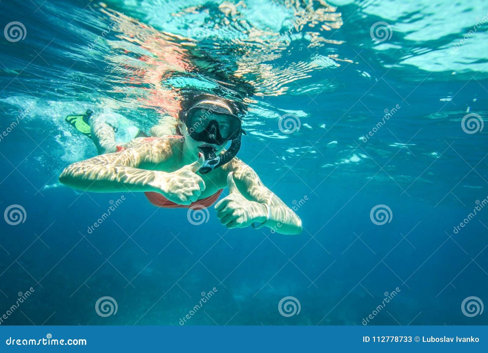 De jonge vrouw snorkelt, tegenhoudend twee duimen