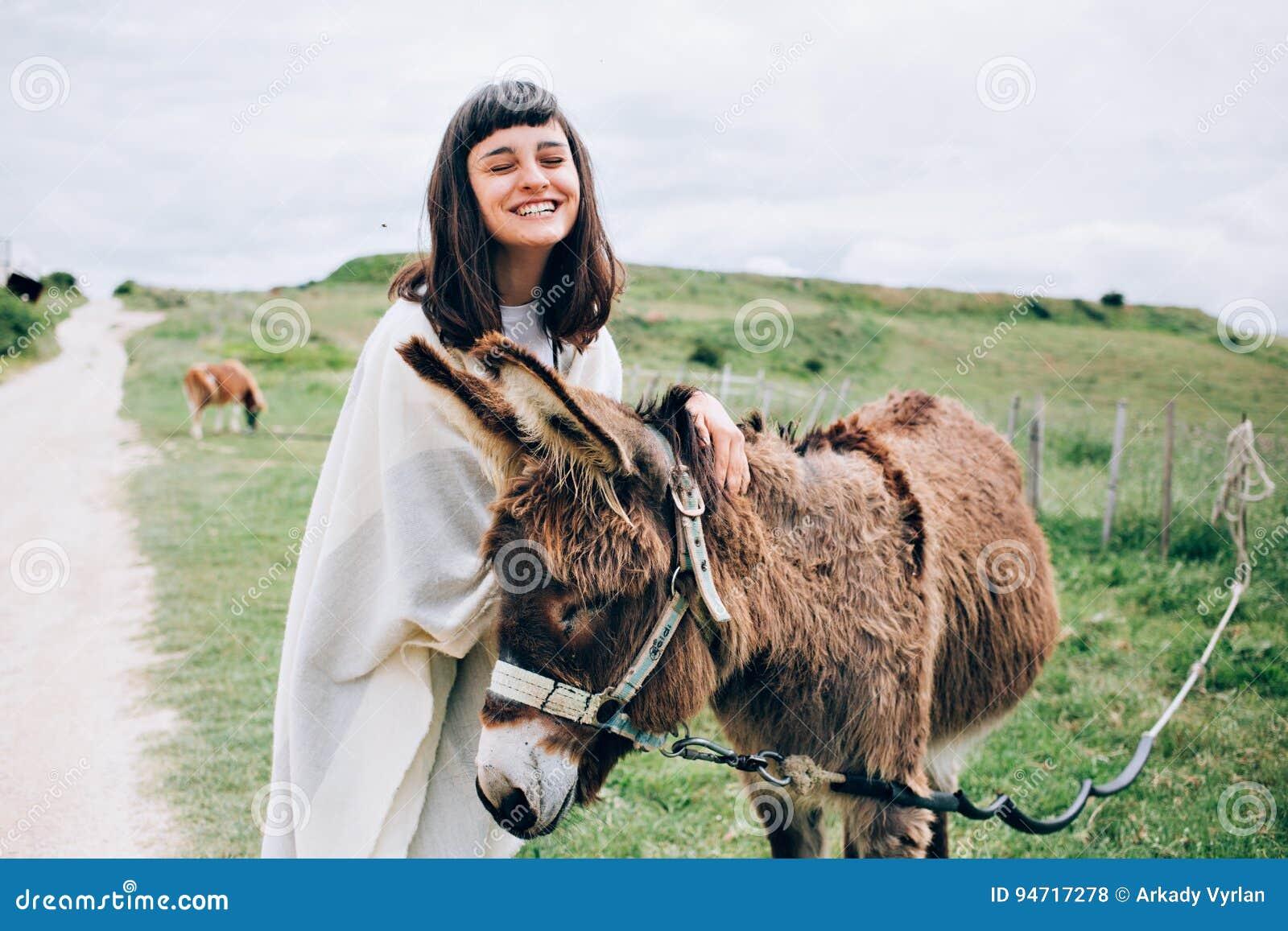 De jonge vrouw streelt een gelukkige ezel