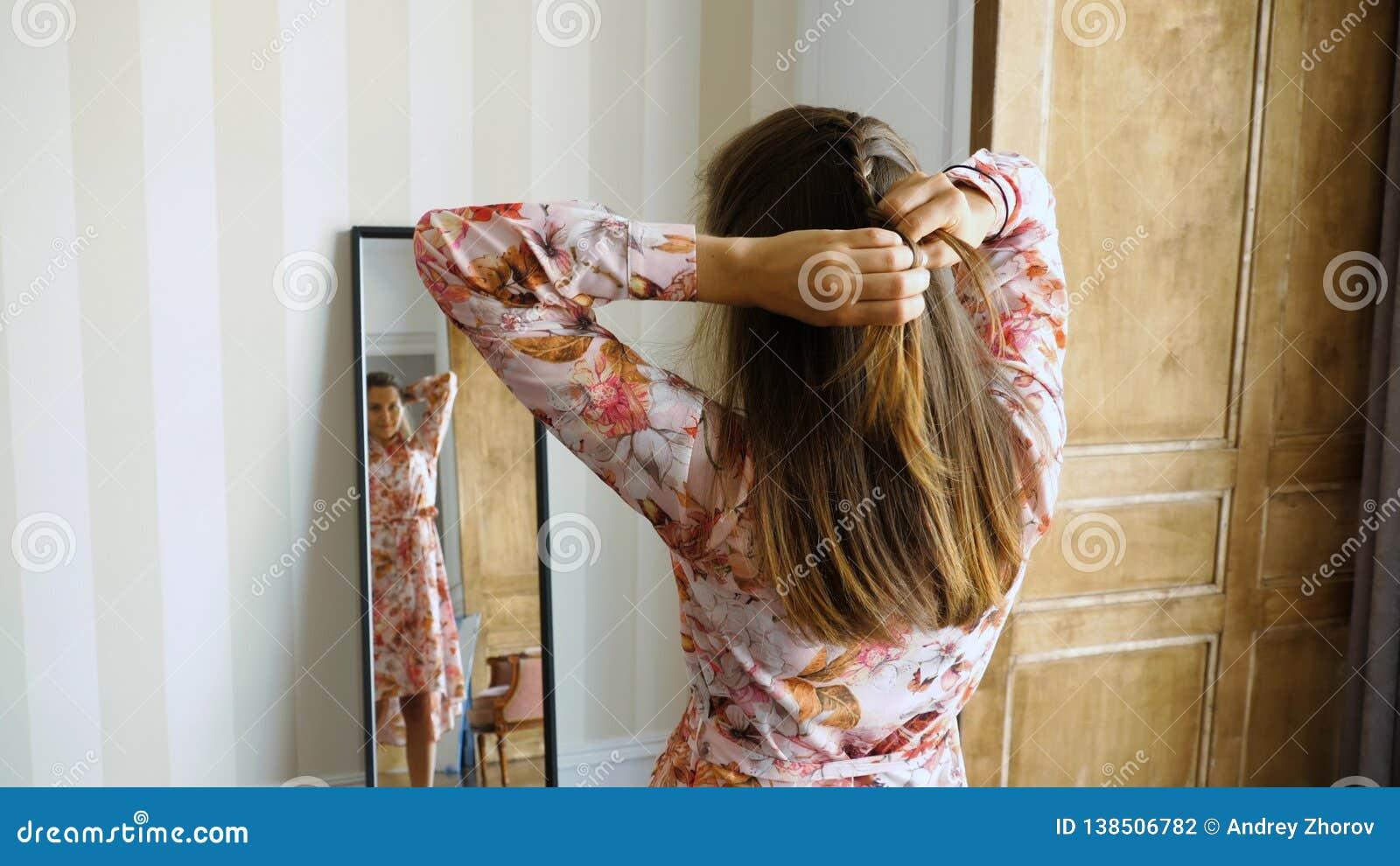 De jonge vrouw vlecht haar haar voor een spiegel