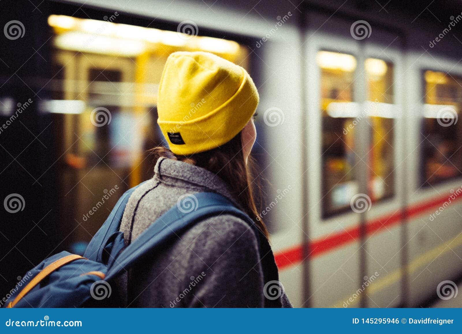 De jonge vrouw wacht bij de metro post terwijl treinarrrives Vervoer en reisconcept