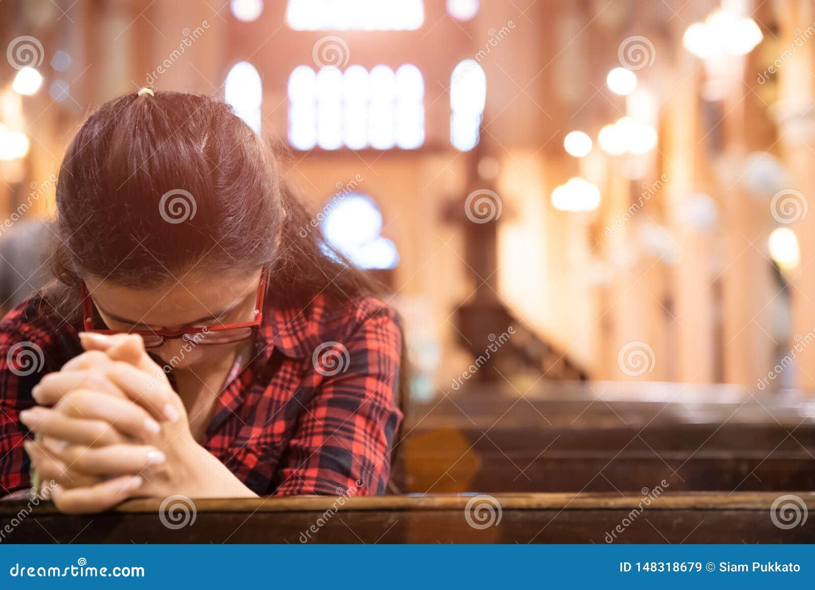 De jonge vrouw zit op een bank in de kerk en bidt aan God Handen die in gebedconcept worden gevouwen voor geloof