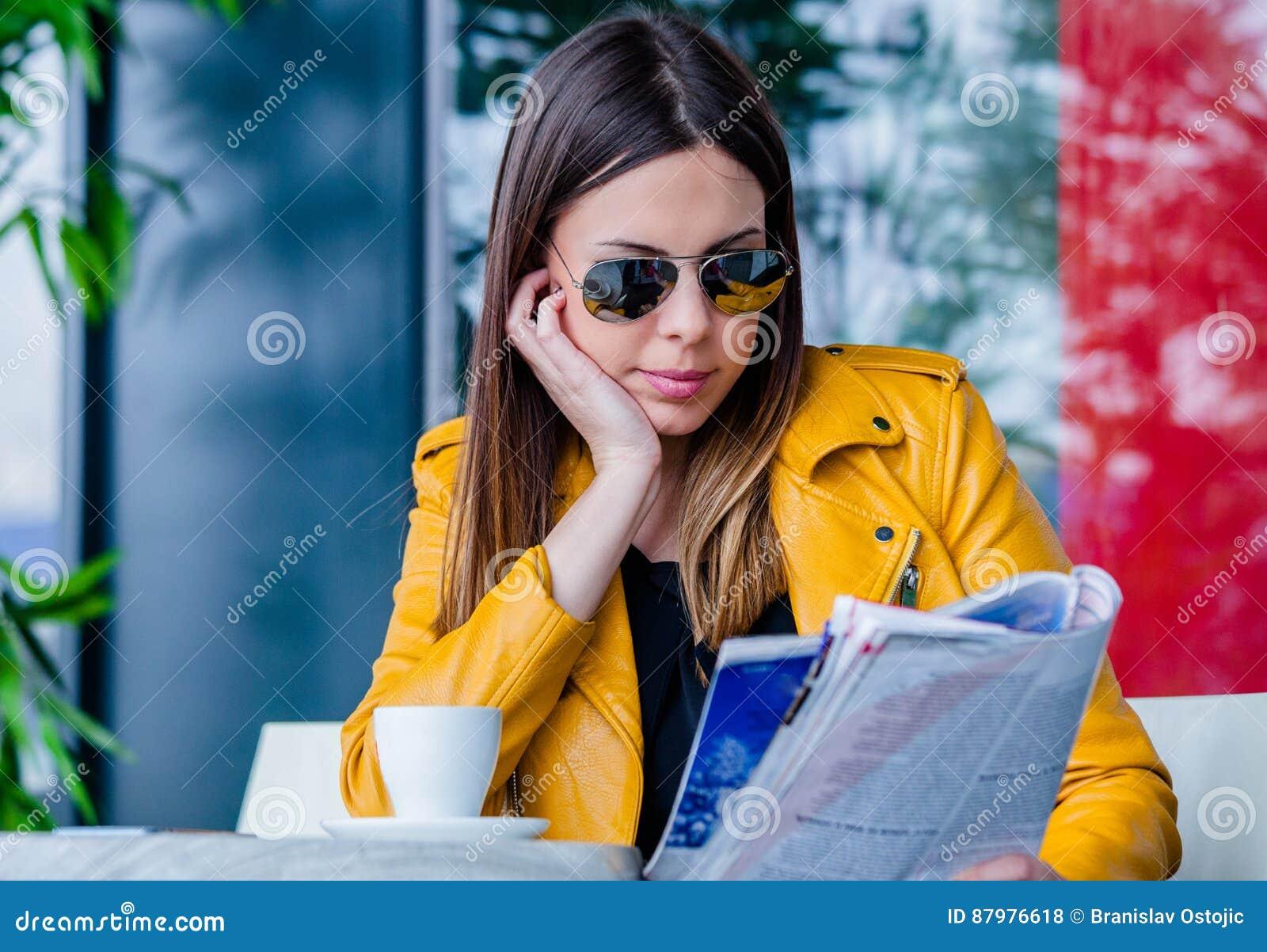 De jonge vrouw zit in tijdschrift van de koffie het openluchtlezing