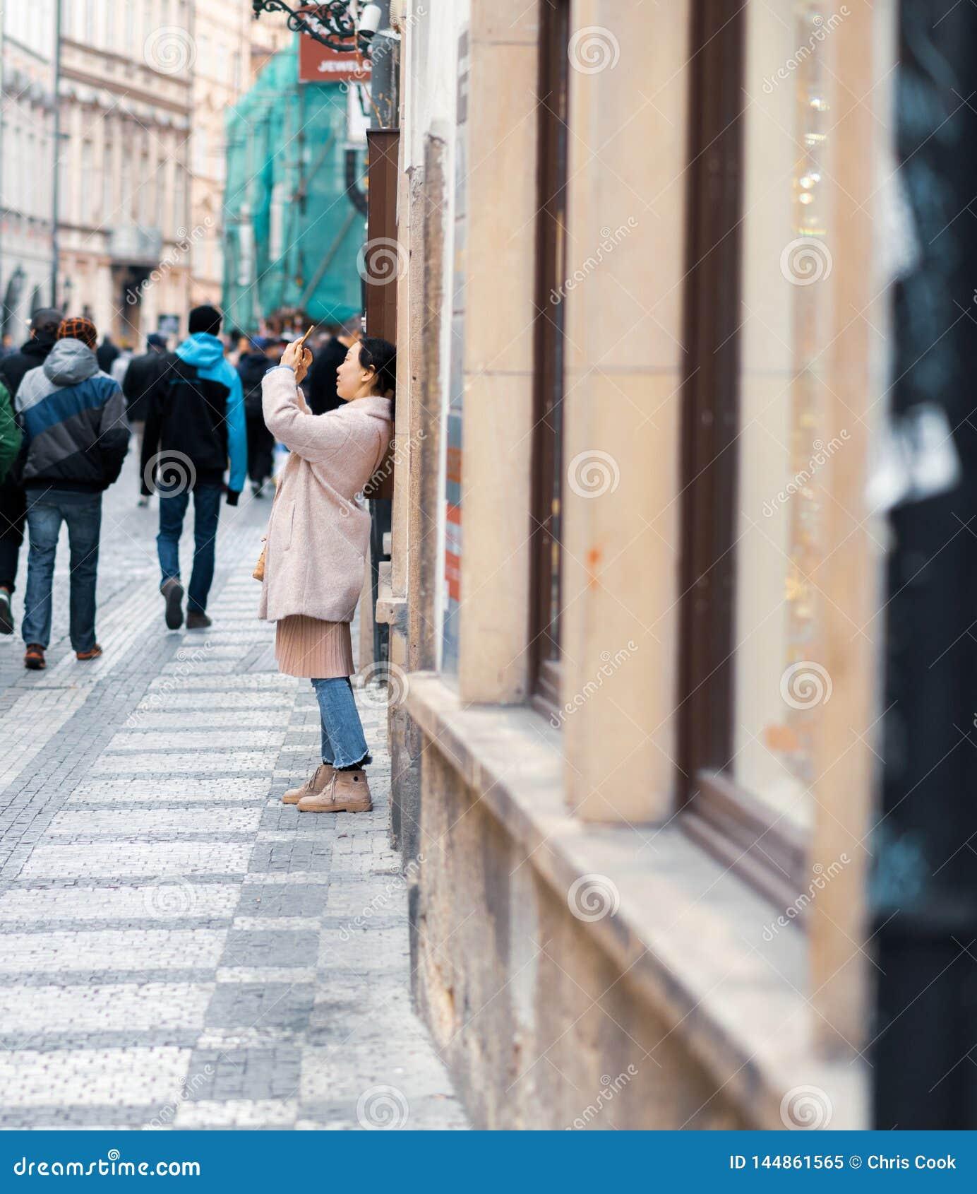 De jonge Vrouwelijke Aziatische toerist neemt foto s terwijl sightseeing in Praag, Tsjechische Republiek - Pasen-Vakantie