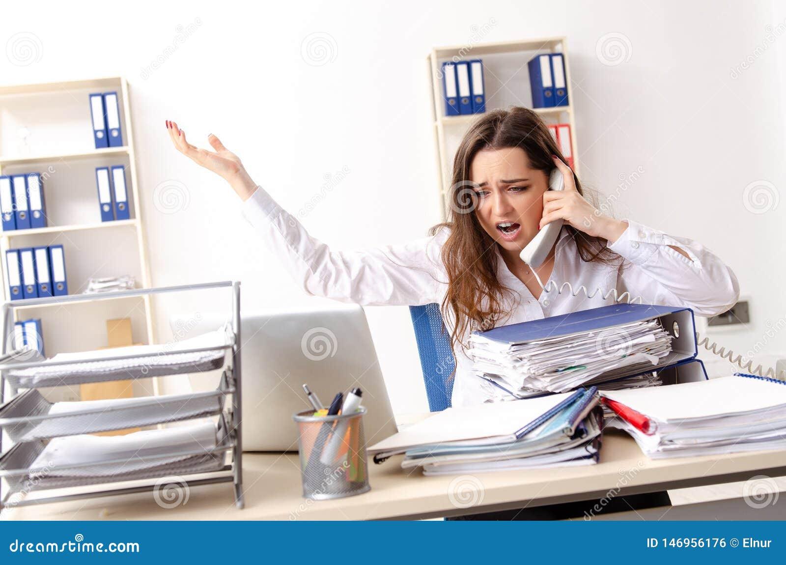 De jonge vrouwelijke werknemer ongelukkig met het bovenmatige werk