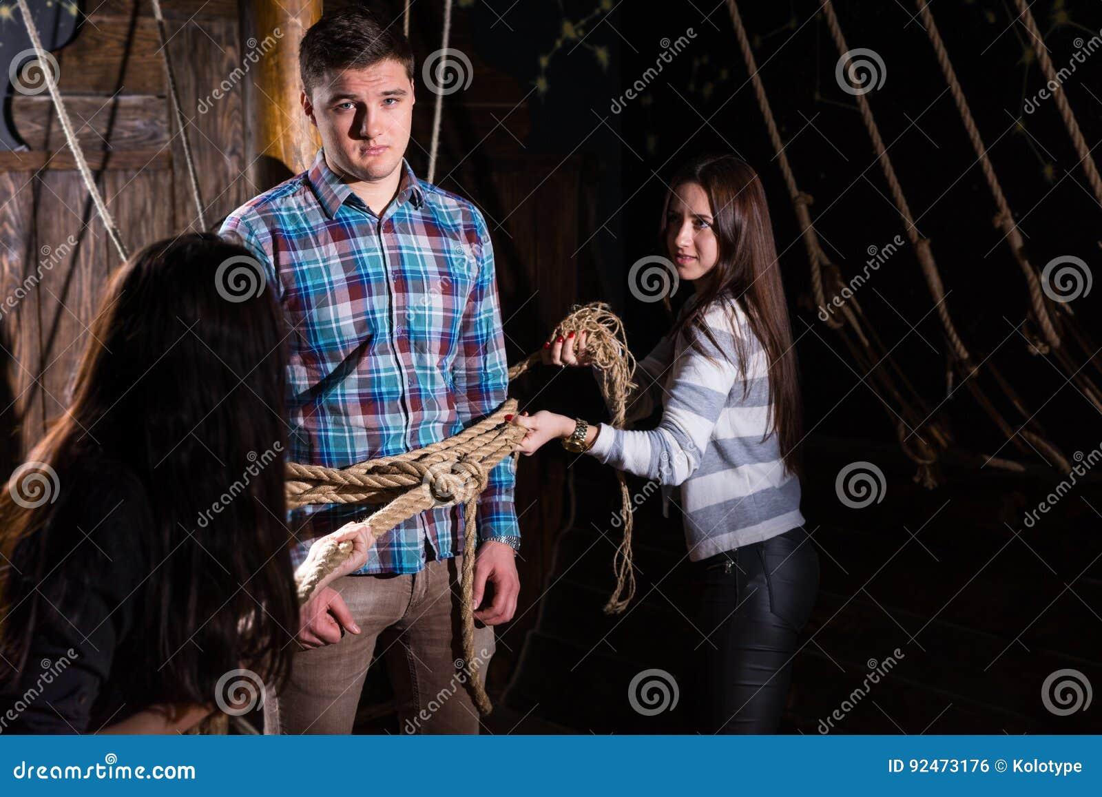 De jonge vrouwen binden een jonge kerel aan een kolom op het dek van een schip