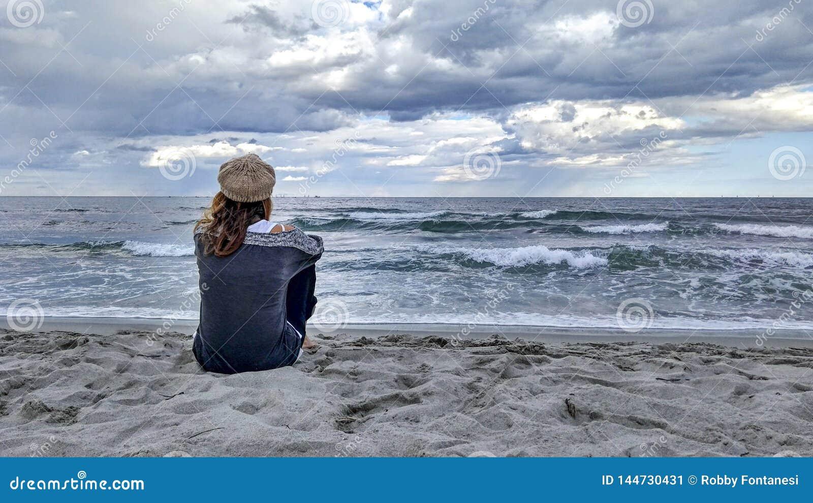 De jonge vrouwenzitting door het overzees met stormachtige hemel, bekijkt zorgvuldig de horizon