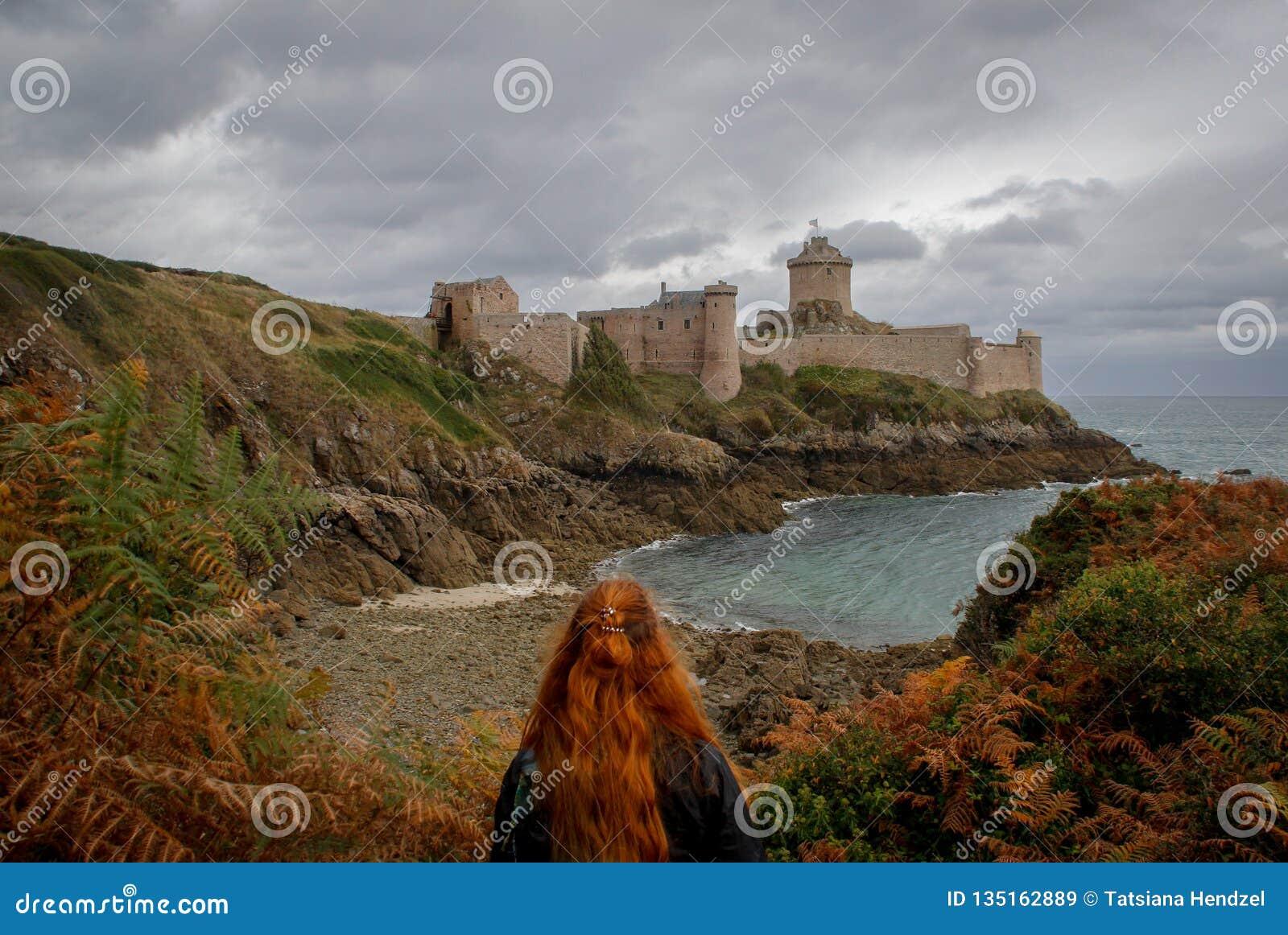 De jonge witte Kaukasische vrouw met lang rood haar bevindt zich tegen de achtergrond van beroemd middeleeuws kasteella Latte van