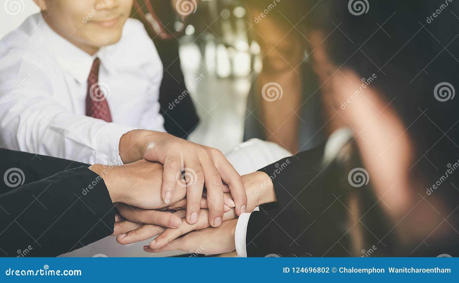 De jonge zakenlieden sluiten aan zich samen bij handen om zaken te leiden togeth