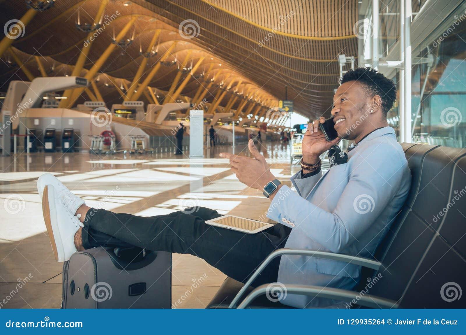 De jonge zakenman is gezet in de luchthaven die en B glimlachen spreken