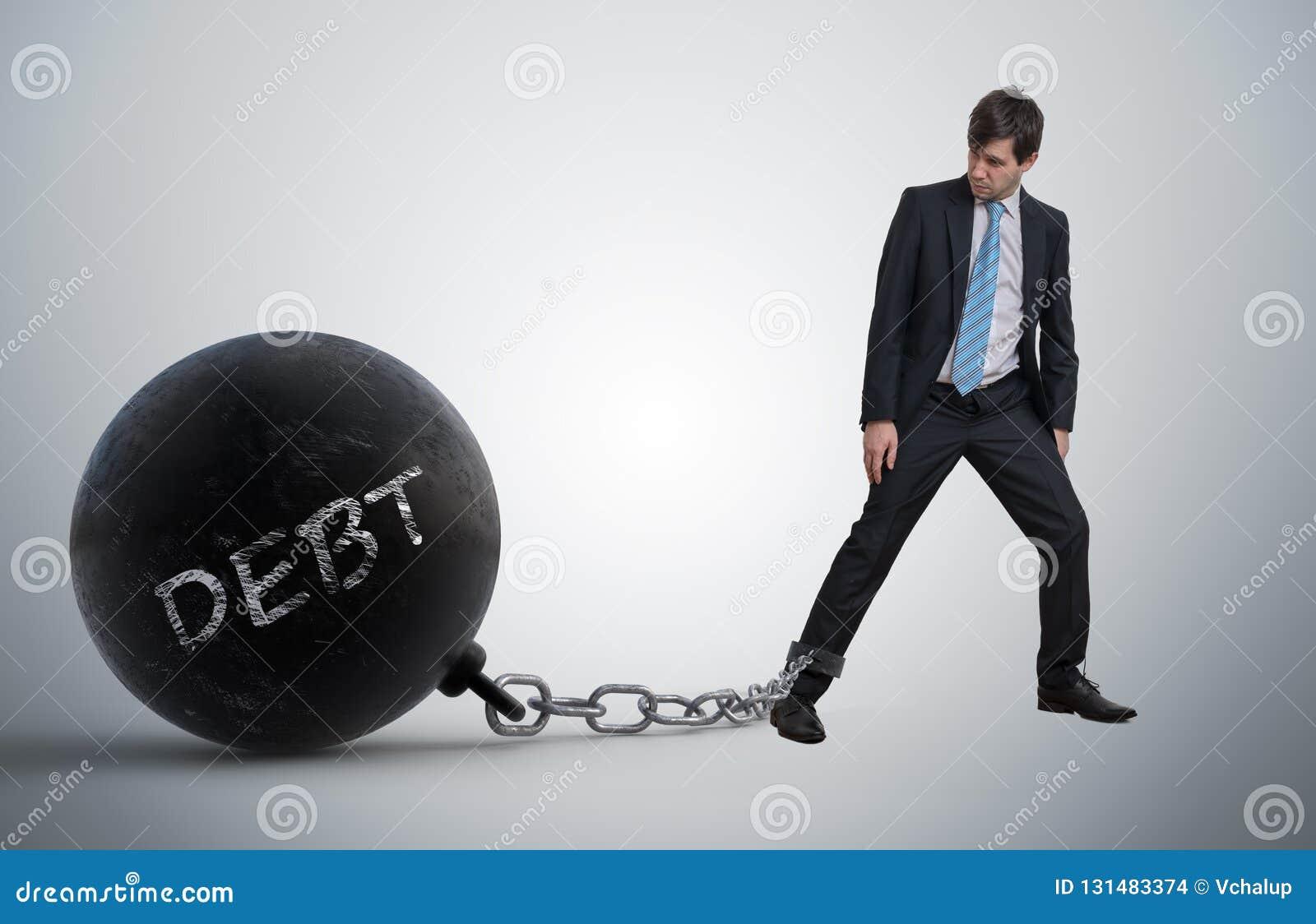 De jonge zakenman heeft grote metaalbal aan zijn been met geschreven schuld geketend