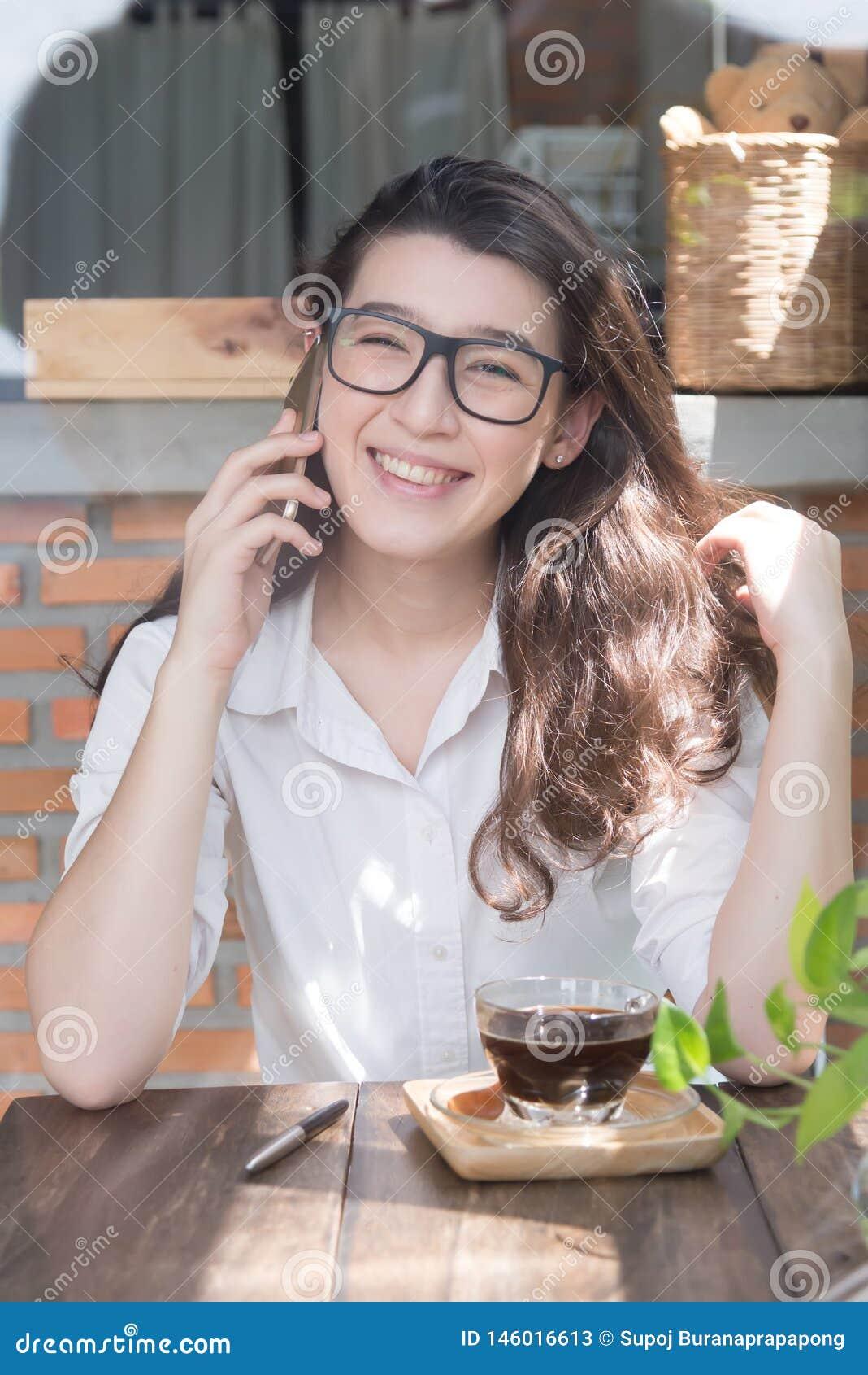 De jonge zitting van de bedrijfsvrouwen vrolijke glimlach bij terraskoffie, die van online mededeling genieten die vrije draadloz