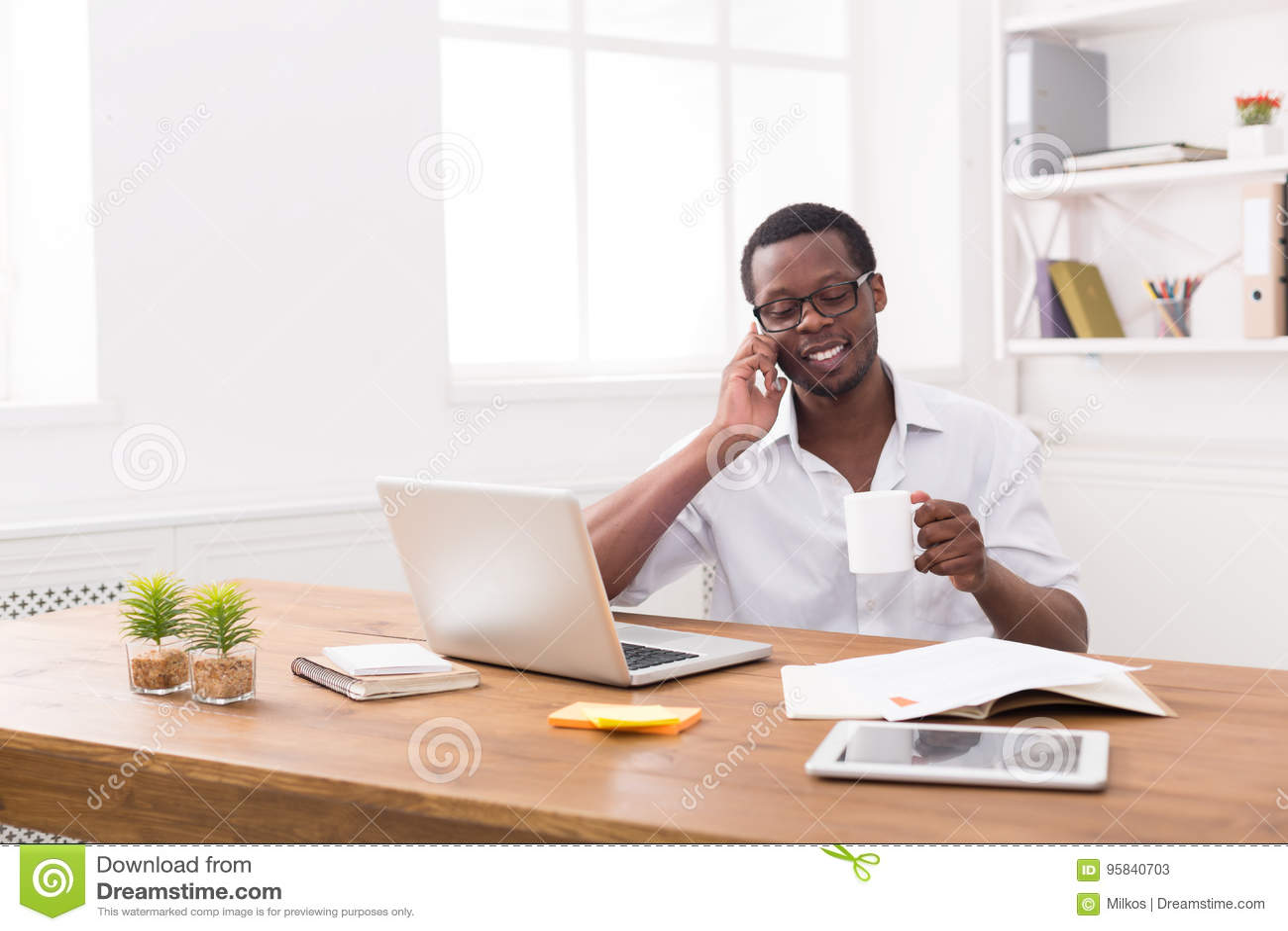 De jonge zwarte mobiele telefoon van de zakenmanvraag in modern wit bureau