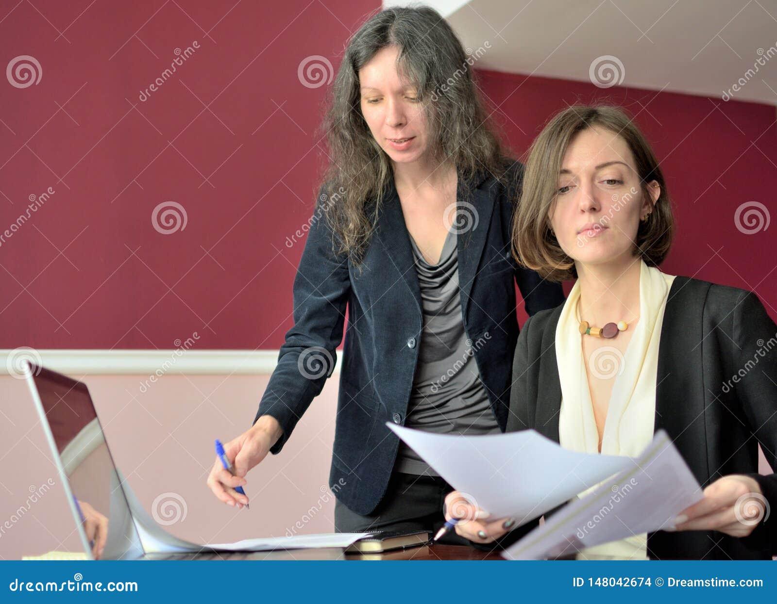 De jongelui kleedde smartly dame helpt een andere jonge dame om met documenten te werken, vormen en teken vullen