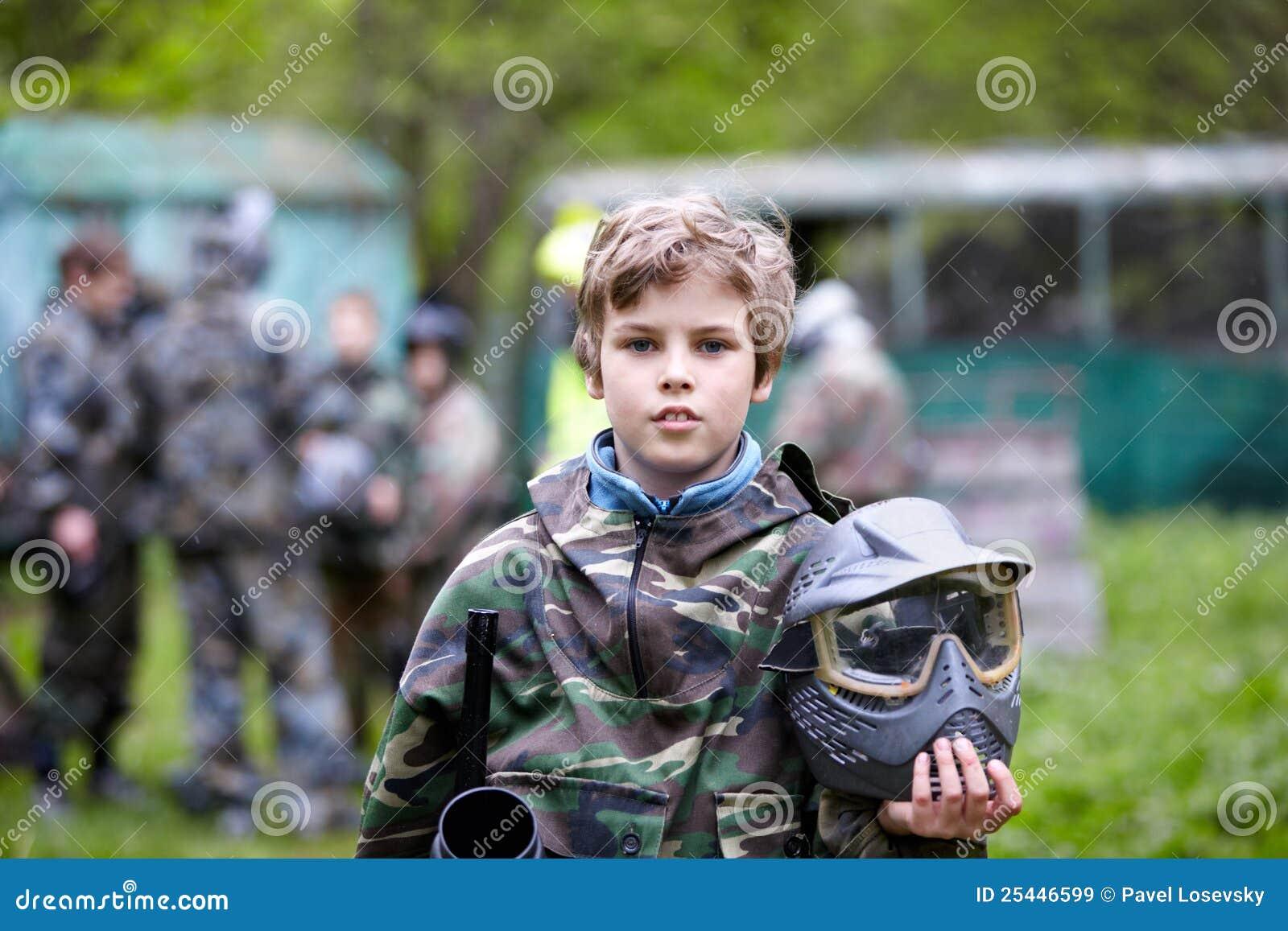 De jongen in camouflage houdt paintball kanonvat tegen