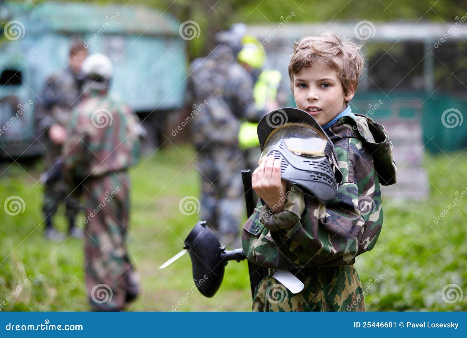 De jongen in camouflage houdt tegen een vat van het paintballkanon