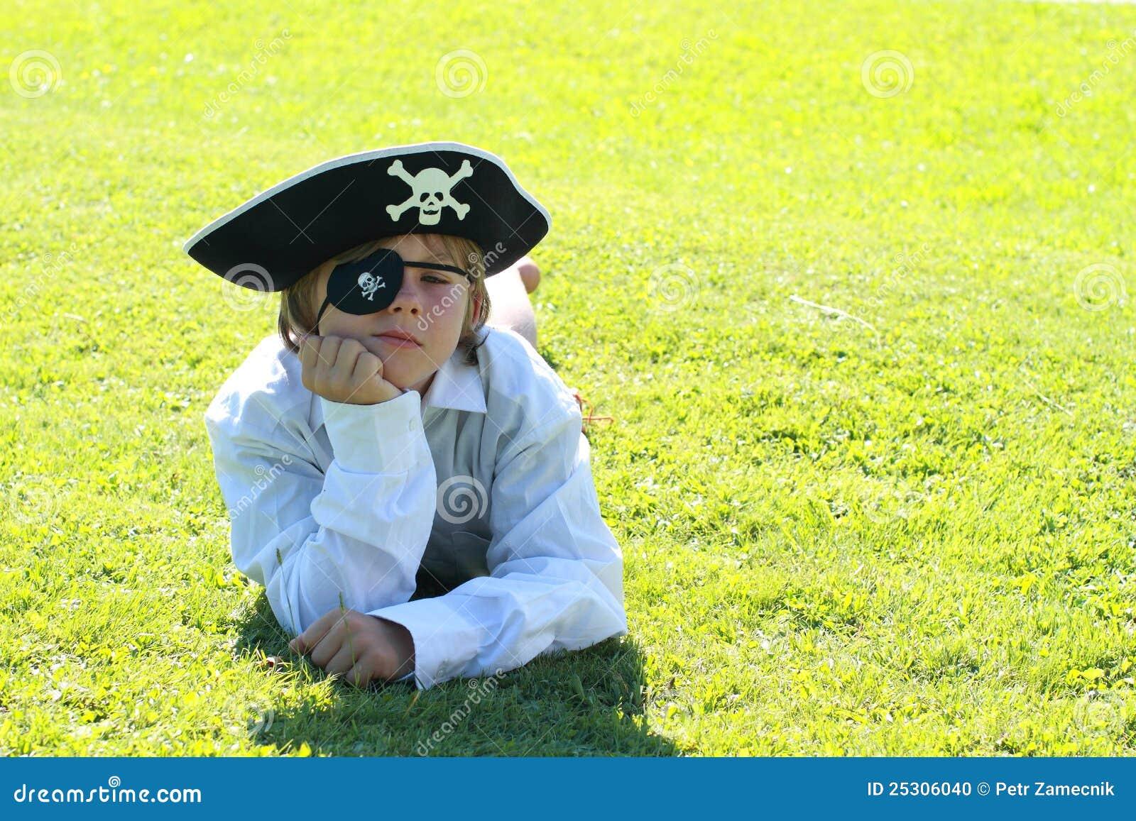 De jongen die van de piraat op gras ligt