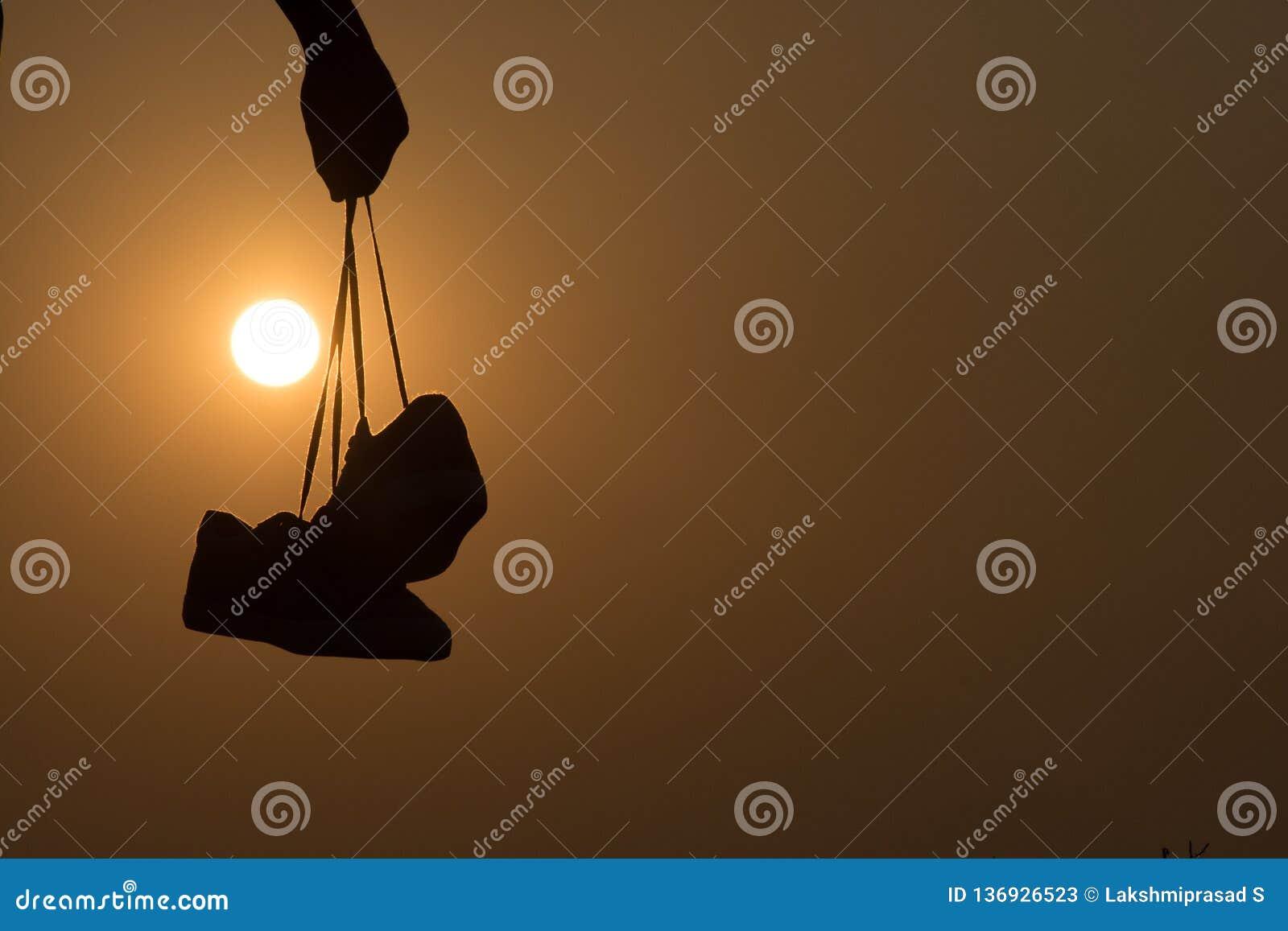 De Jongen die zich bij zonsondergang bevinden en schoenen in zijn hand houden Close-up