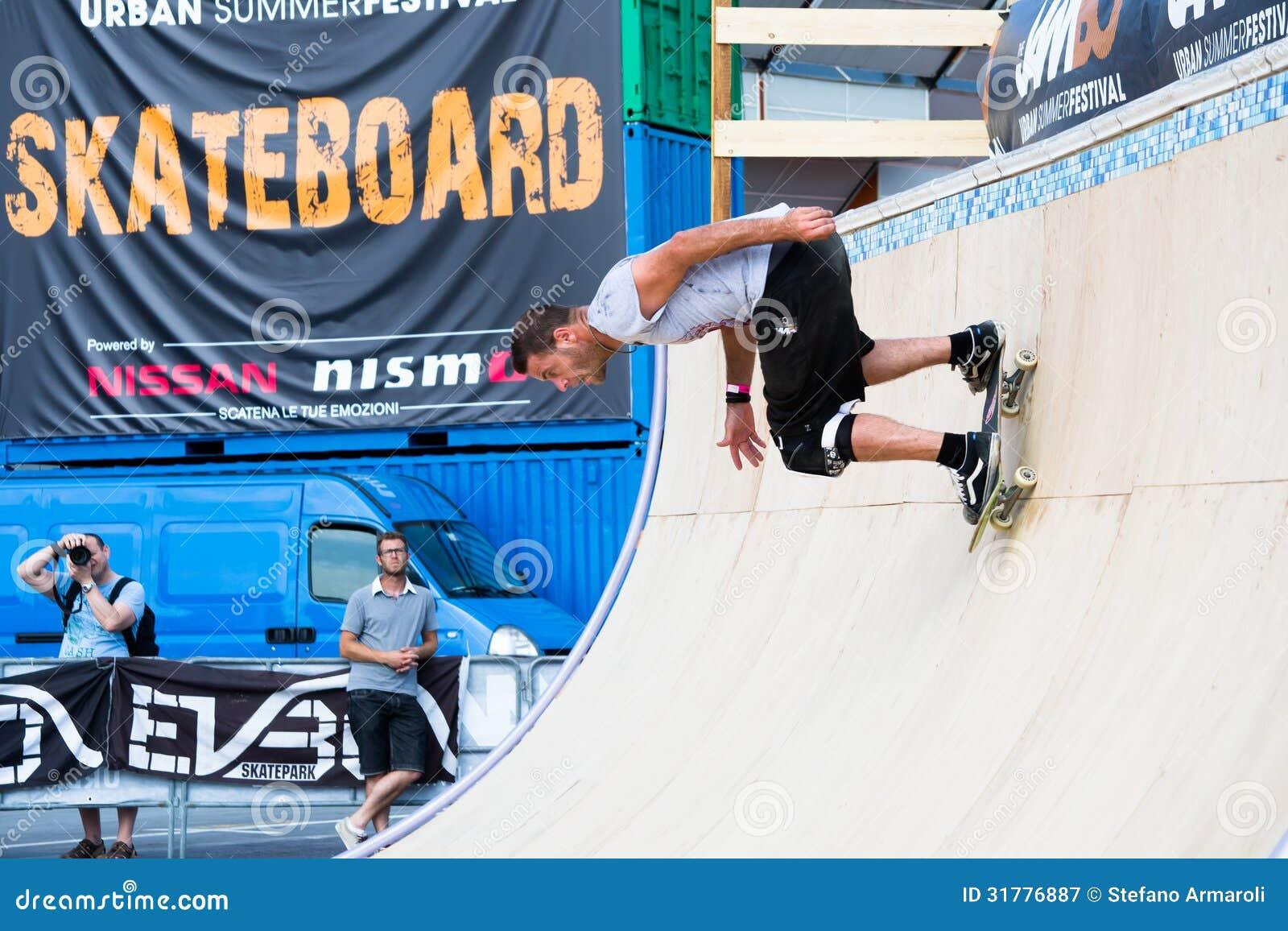 De jongen doet trucs met het skateboard op een helling