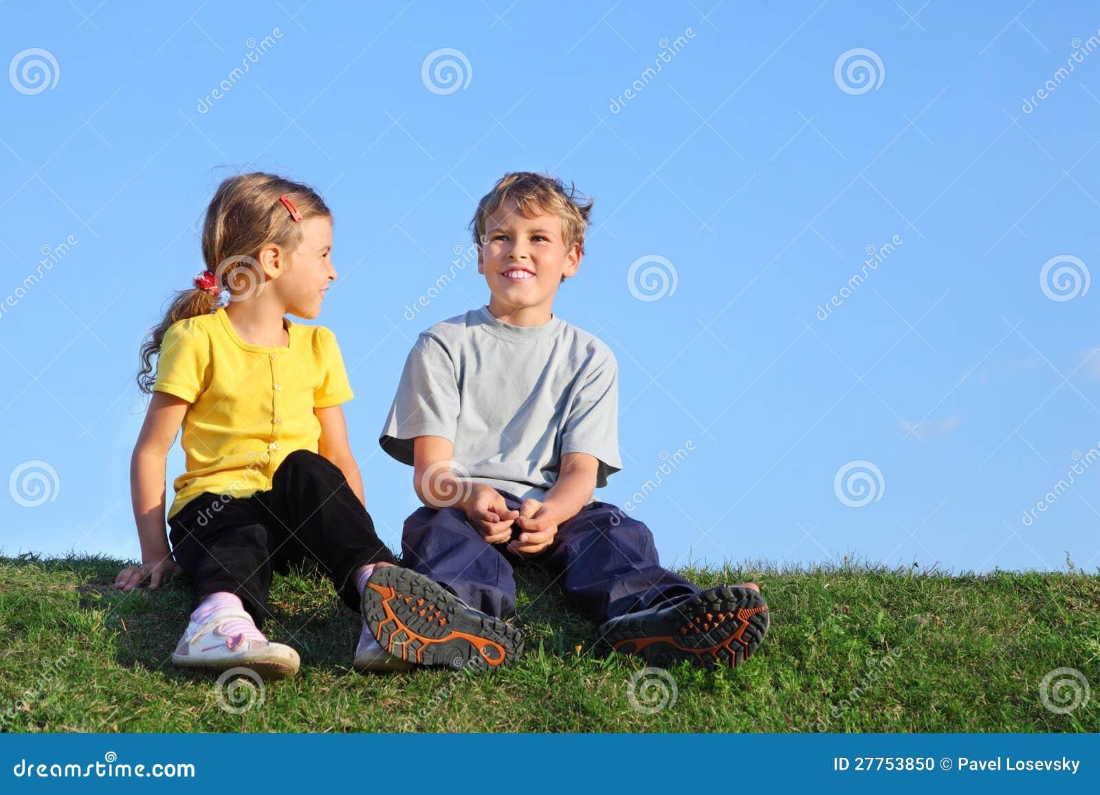 de jongen en het meisje zitten samen op gras stock foto. Black Bedroom Furniture Sets. Home Design Ideas