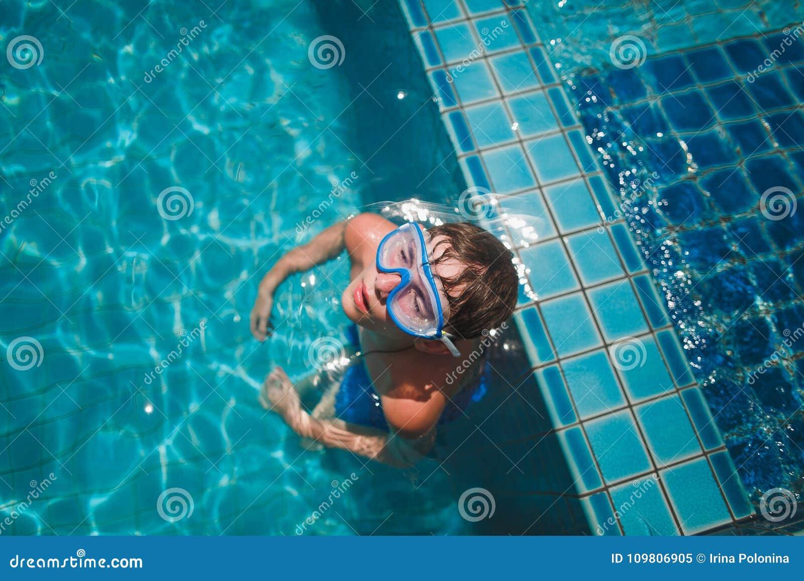 De jongen in het masker voor het zwemmen in de pool met blauw water Hij ontspant met gesloten ogen Op het gezichts blauwe masker