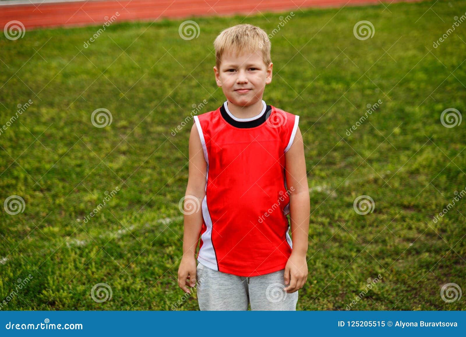 De jongen in het rode vest die zich op groen gras bevinden