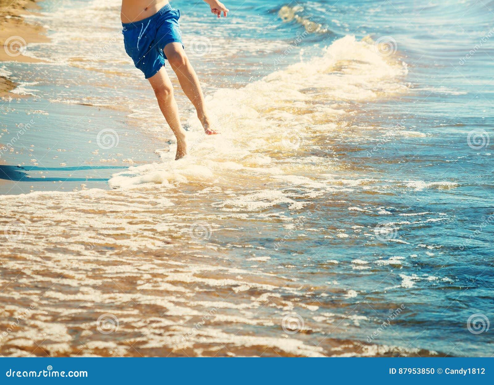 De jongen loopt op het strand
