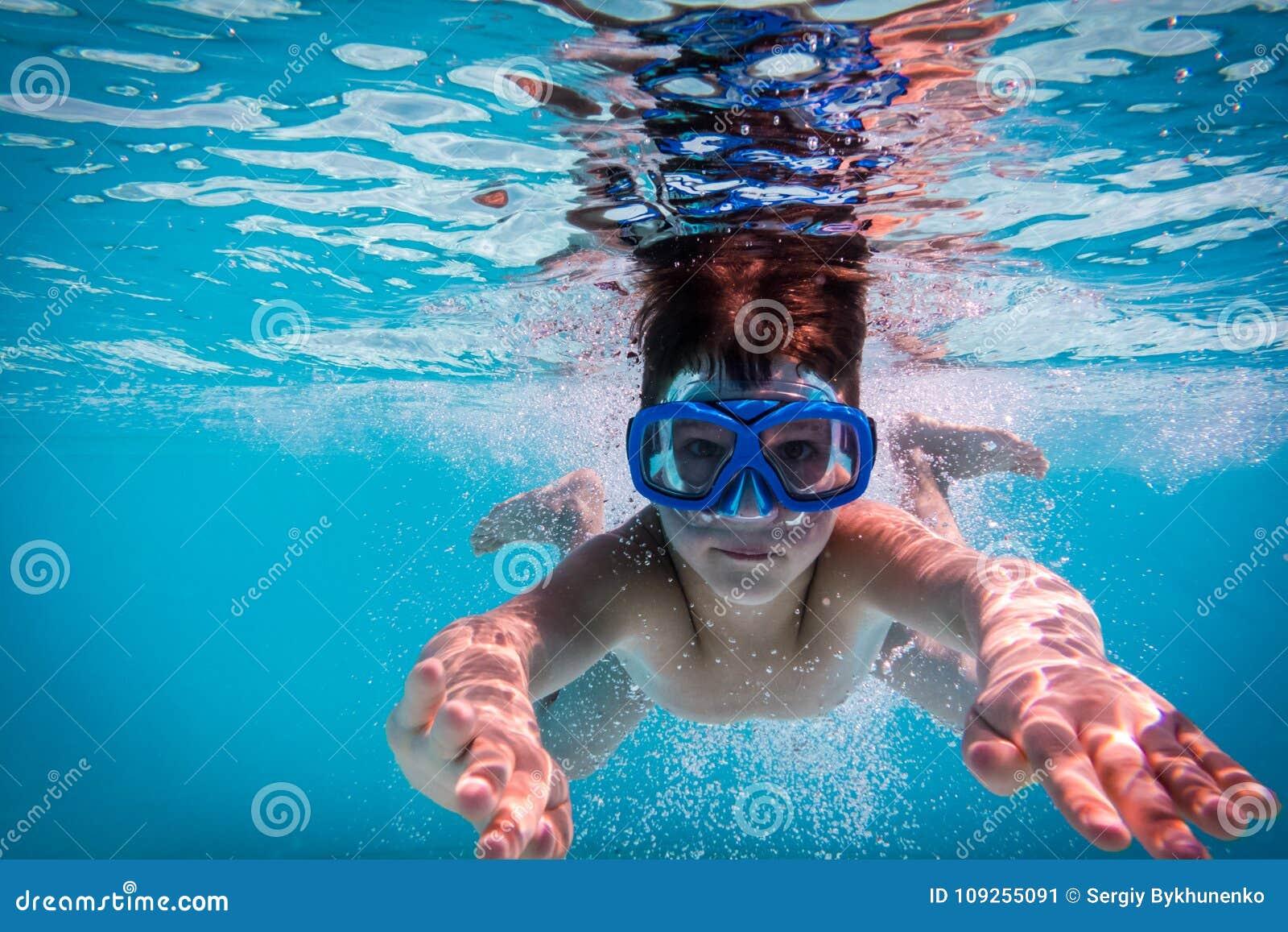 De jongen in masker duikt in zwembad
