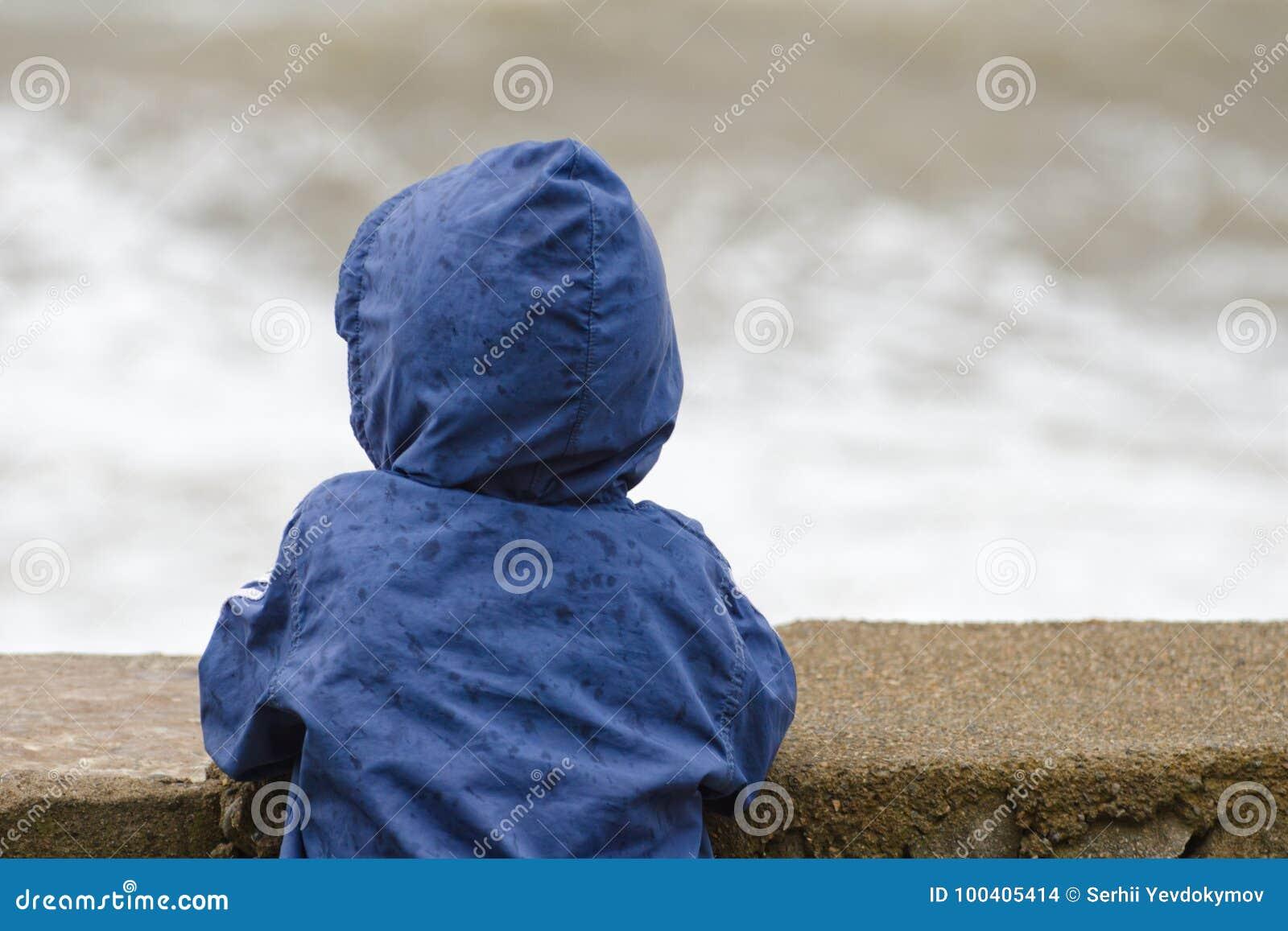 De jongen in matroos met kap bevindt zich met zijn rug tegen de pijler tegen de achtergrond van overzeese golven
