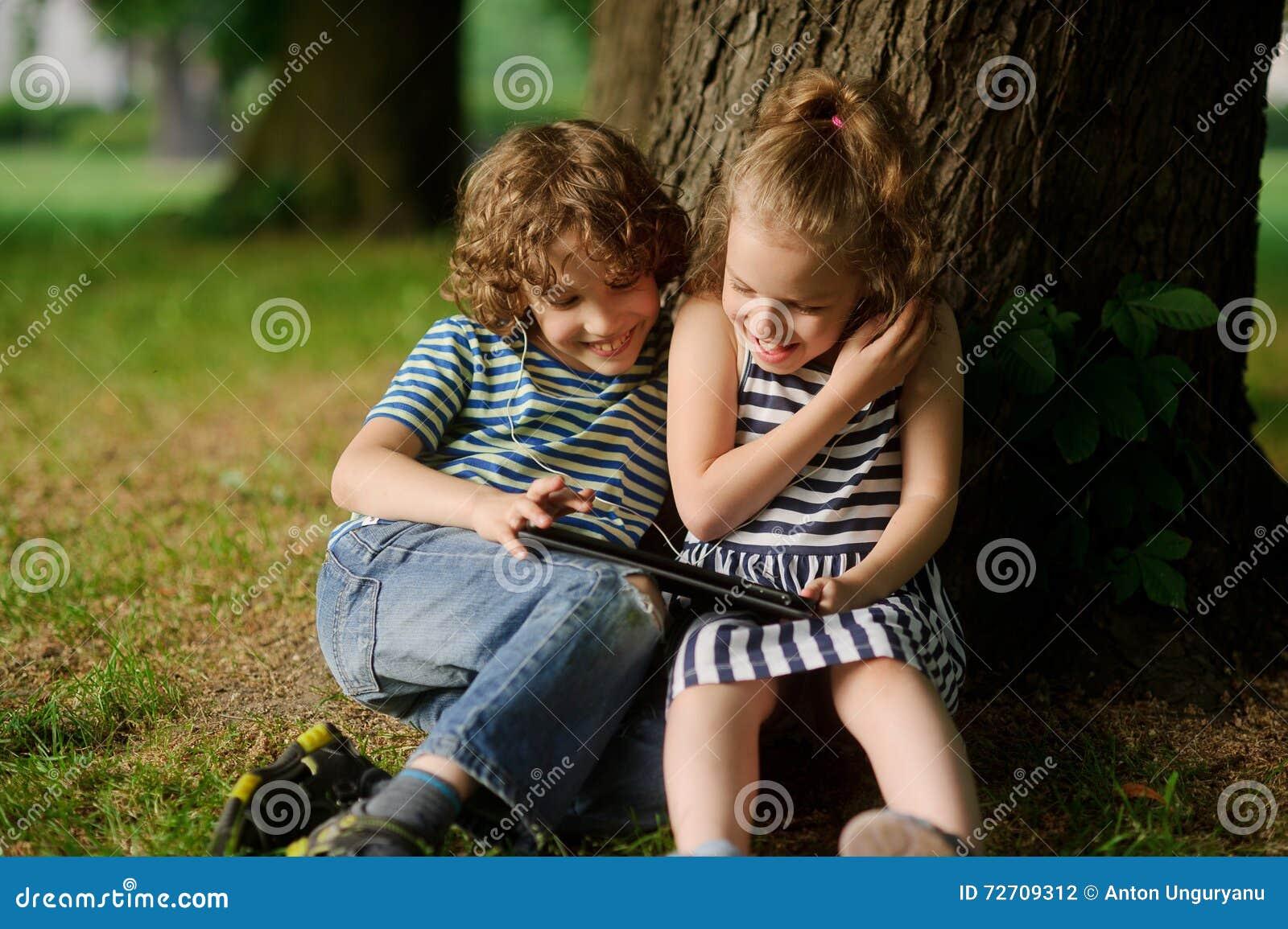 De jongen met meisje van 7 8 jaar zit onder een oude boom en bekijkt excitedly het laptop scherm - Jaar oude meisje kamer foto ...