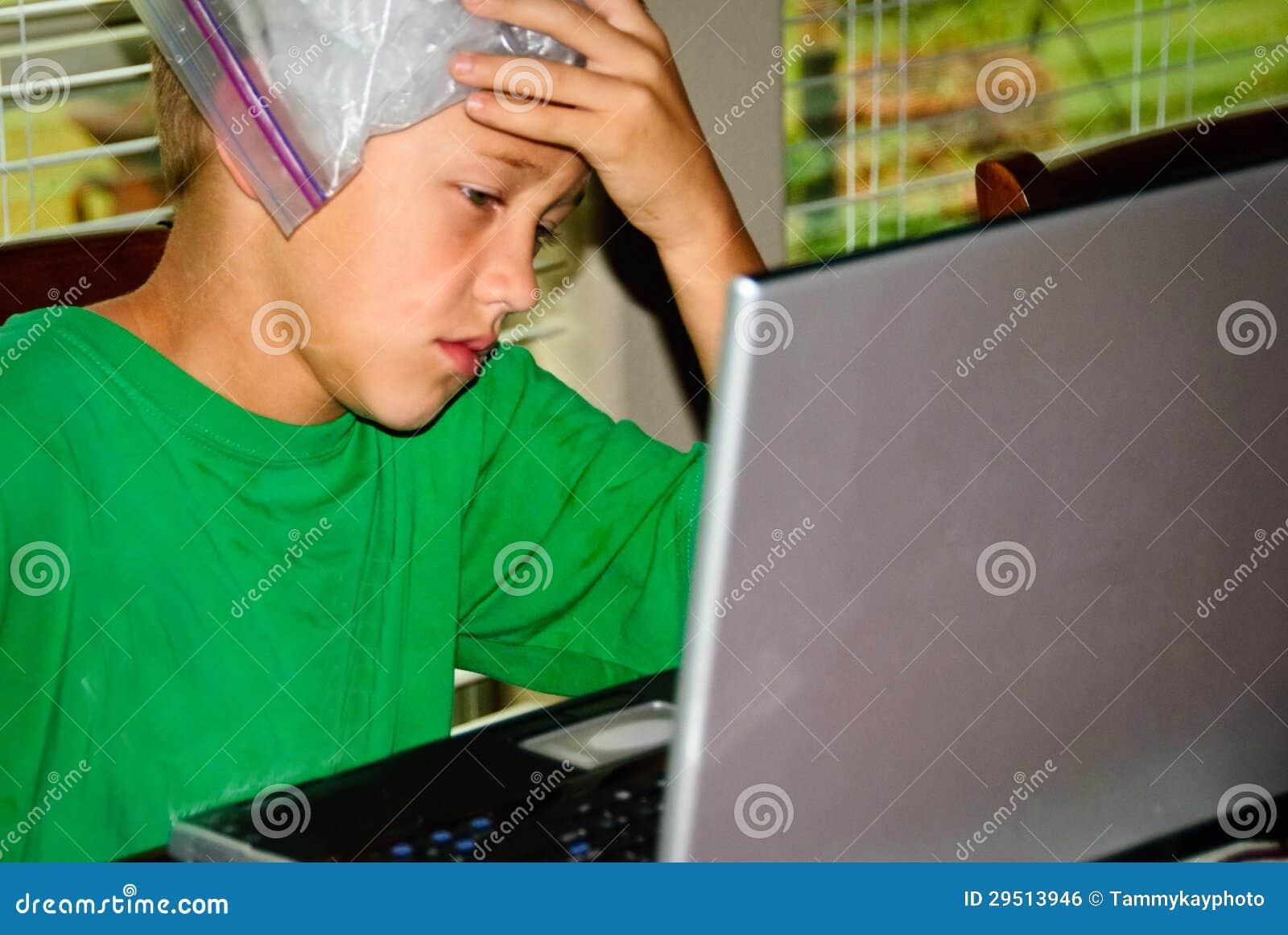 De jongen op laptop beklemtoonde met hoofdpijn